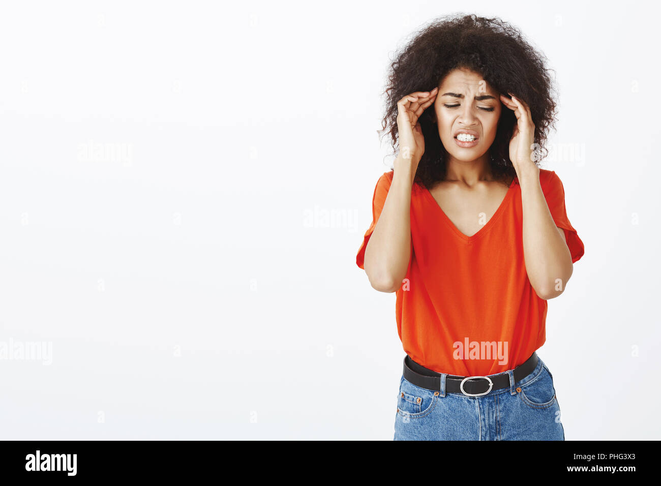 Poor girl having terrible headache. Studio shot of upset european female with afro haircut, touching temples and frowning, grimacing from pain, suffering migraine and standing unfocused - Stock Image