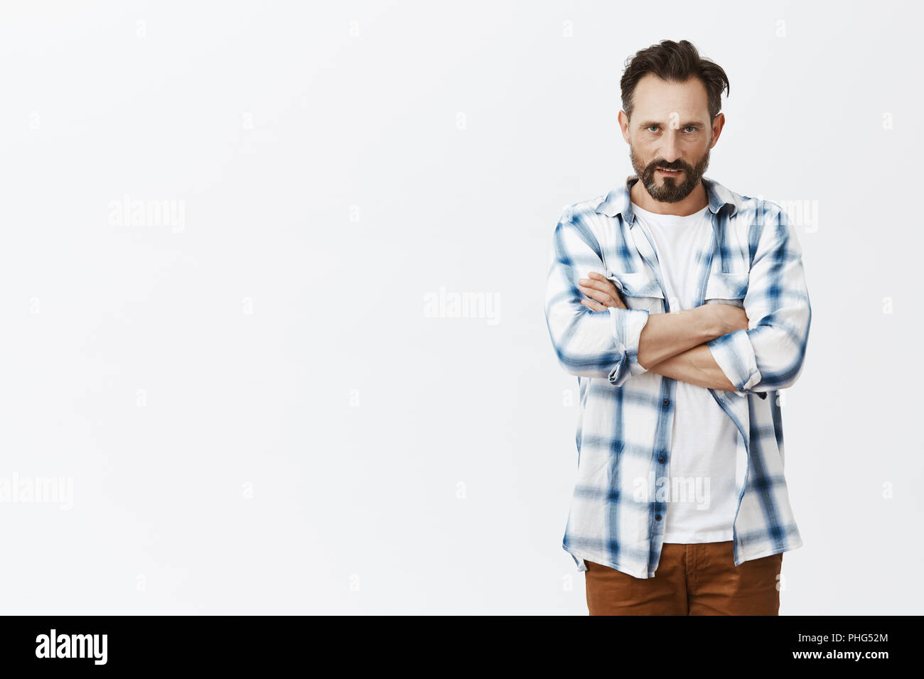 Guy feeling scorn, closing himself from people, standing in defending pose with hands crossed on chest, looking with hate and anger from under forehead at camera, expressing contempt over grey wall - Stock Image