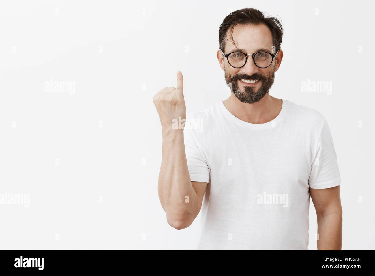 Pinky swear. Portrait of friendly charming adult man in stylish glasses and white t-shirt showing finger and smiling broadly at camera, making promise or make it up with friend over gray background - Stock Image