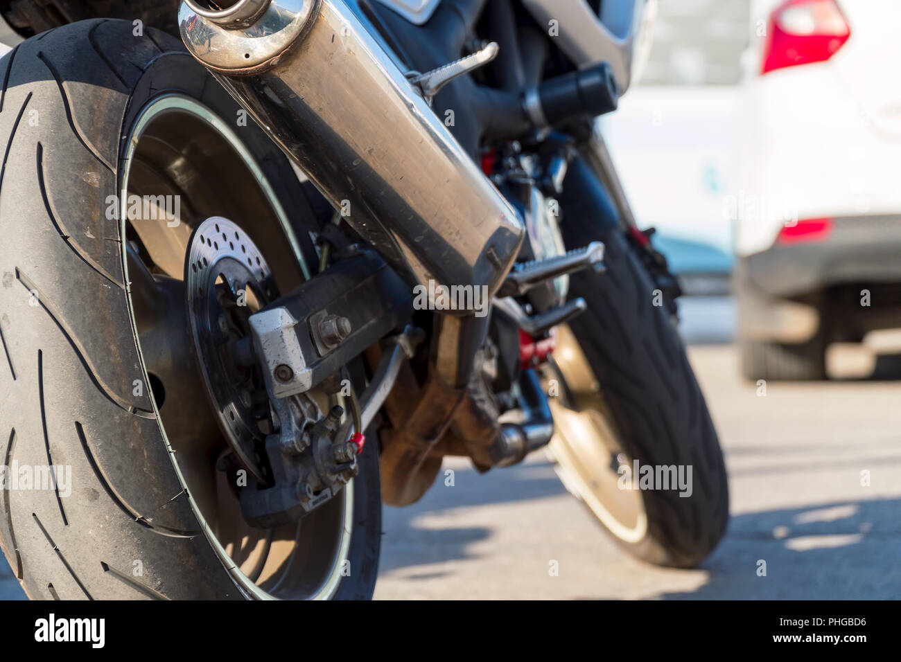 Rear view of motorcycle. Rear wheel, exhaust pipe. Soft focus, blurred background. - Stock Image