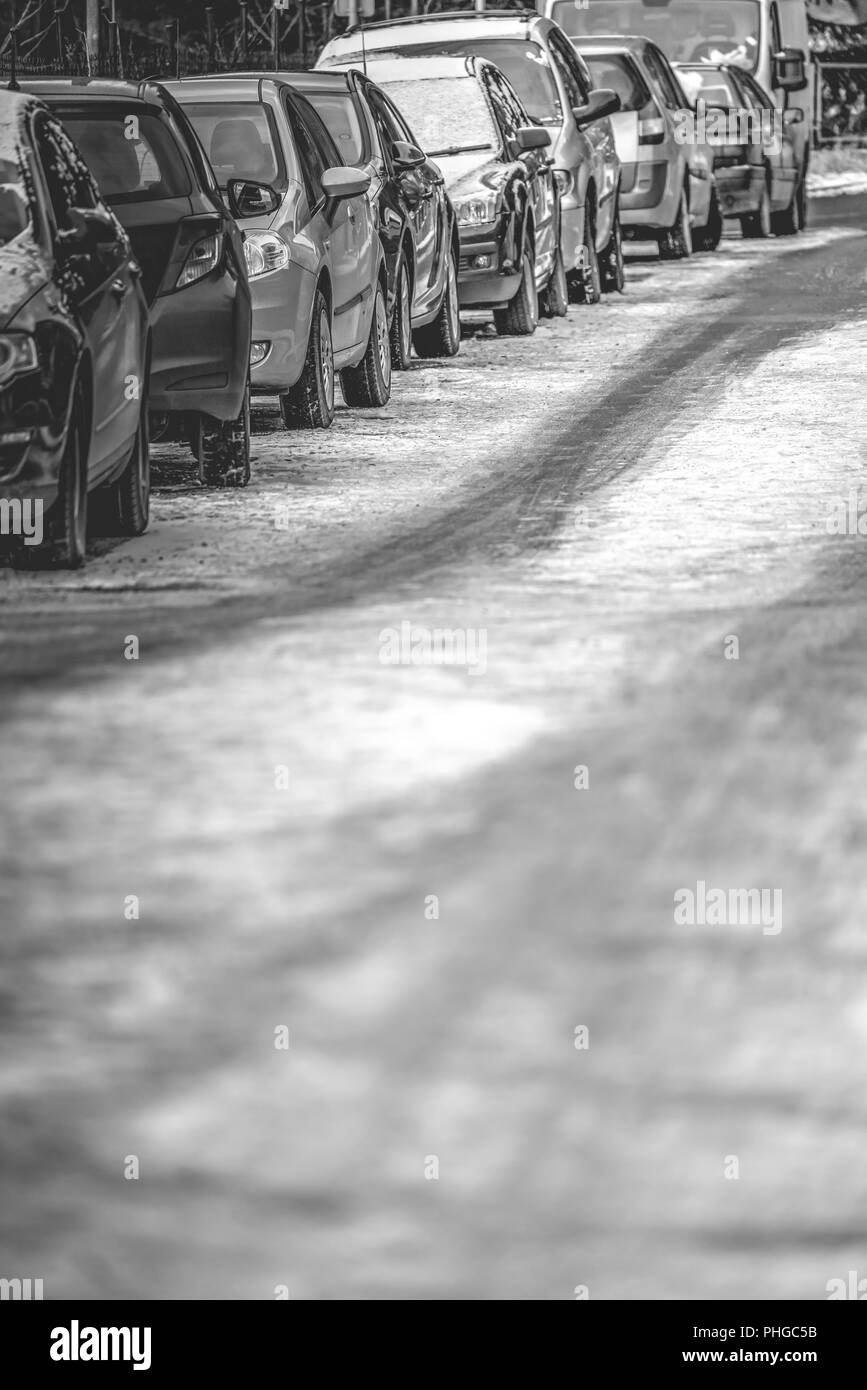 Row of cars parked on the roadside - Stock Image