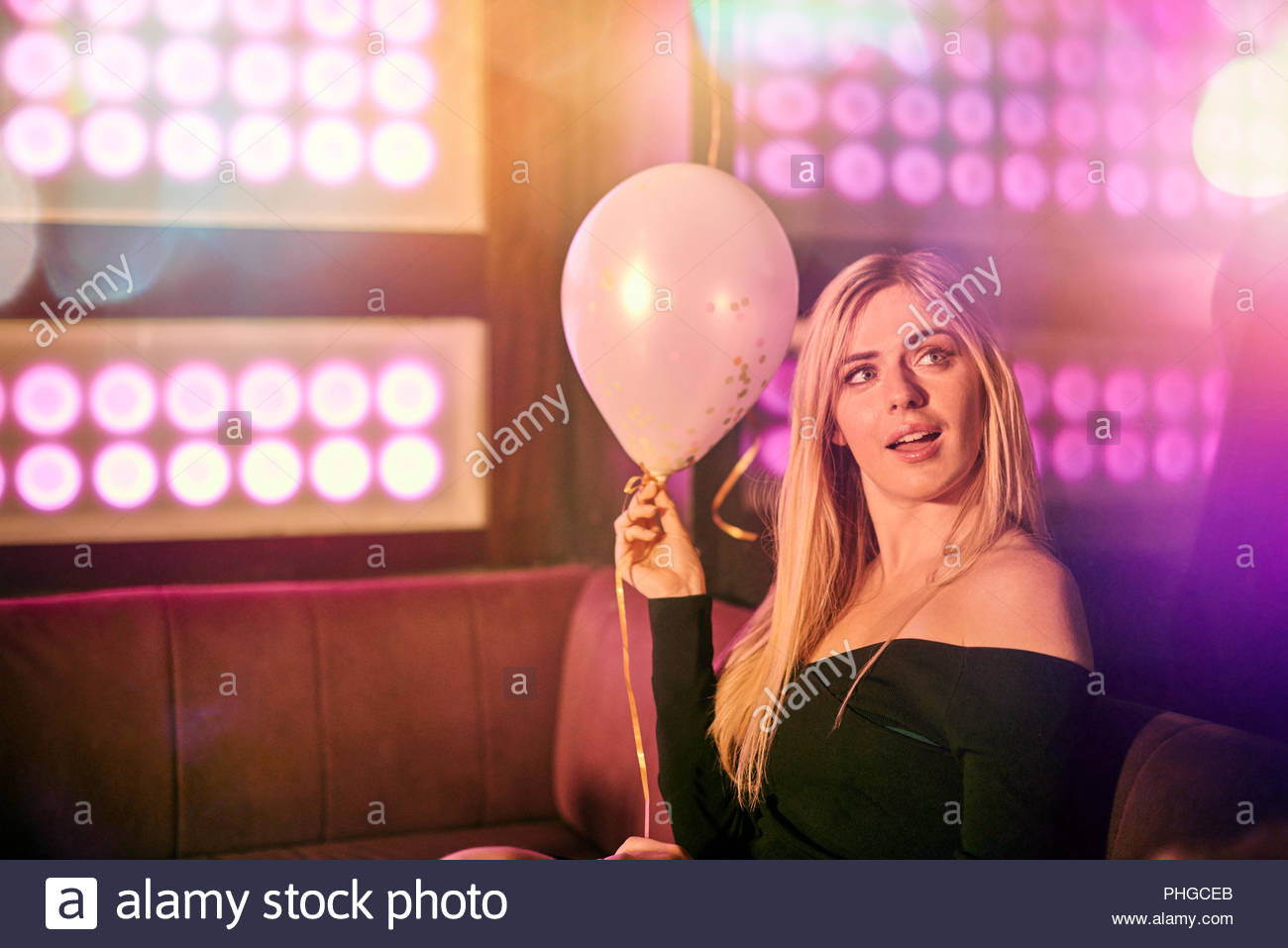 Young woman with balloon at nightclub Stock Photo