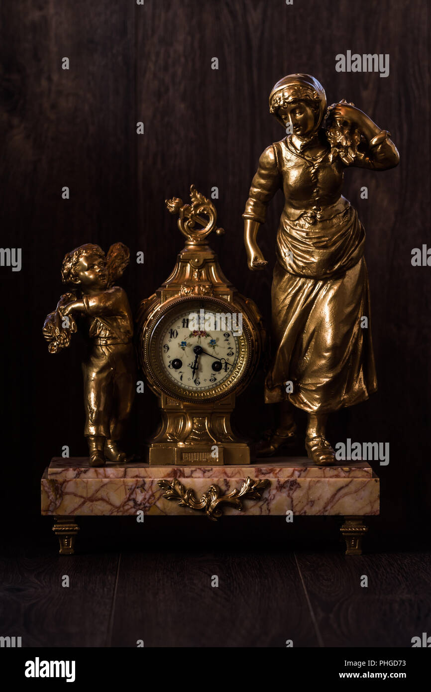 Decorative brass clock with marble pedestal and figurines Stock Photo