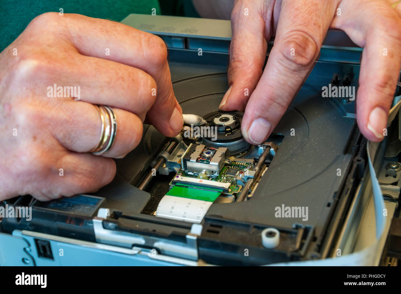 Technician cleaning spindle of a DVD recorder with a cotton bud. - Stock Image
