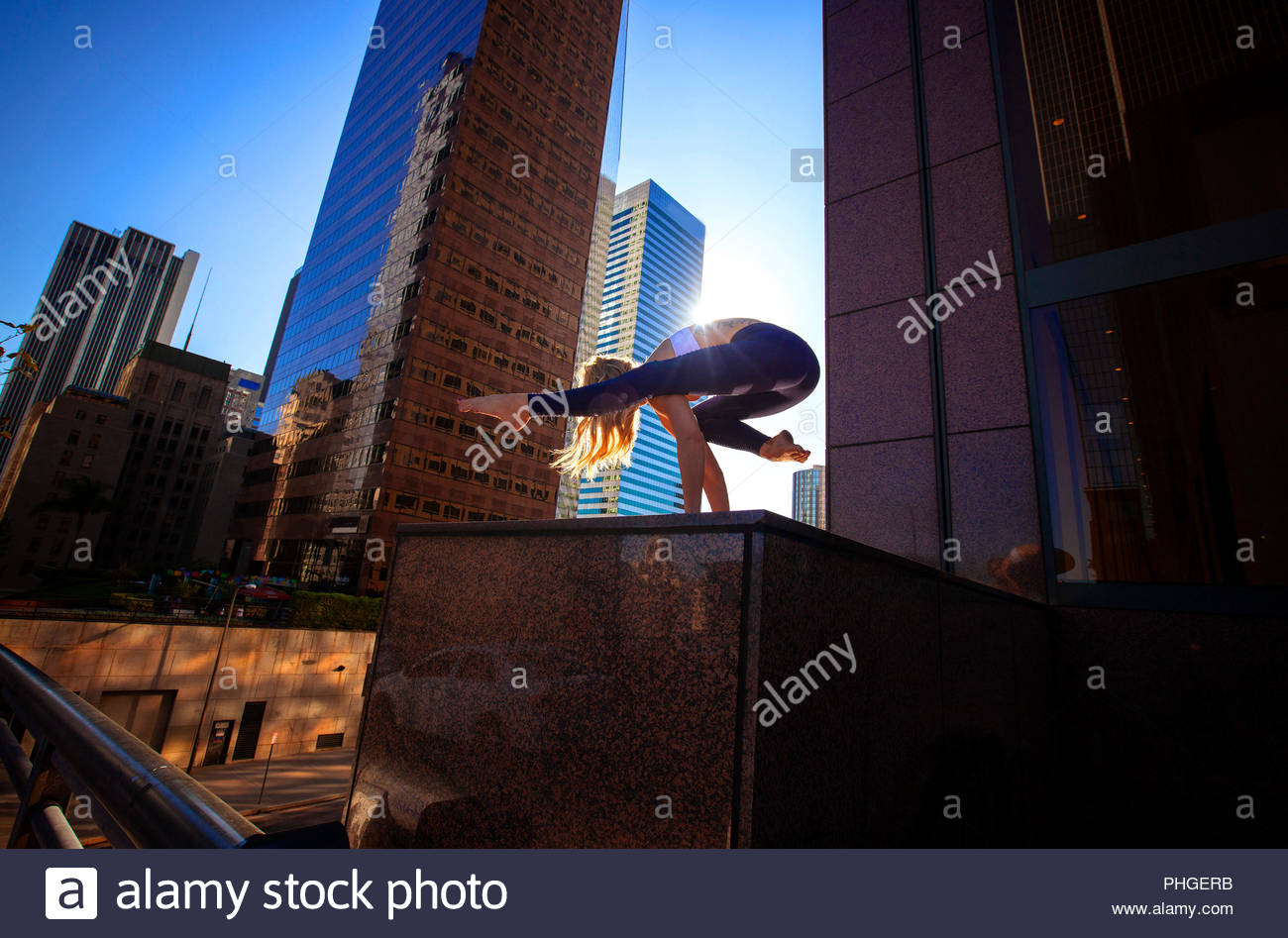 Young woman doing yoga on city rooftop Stock Photo