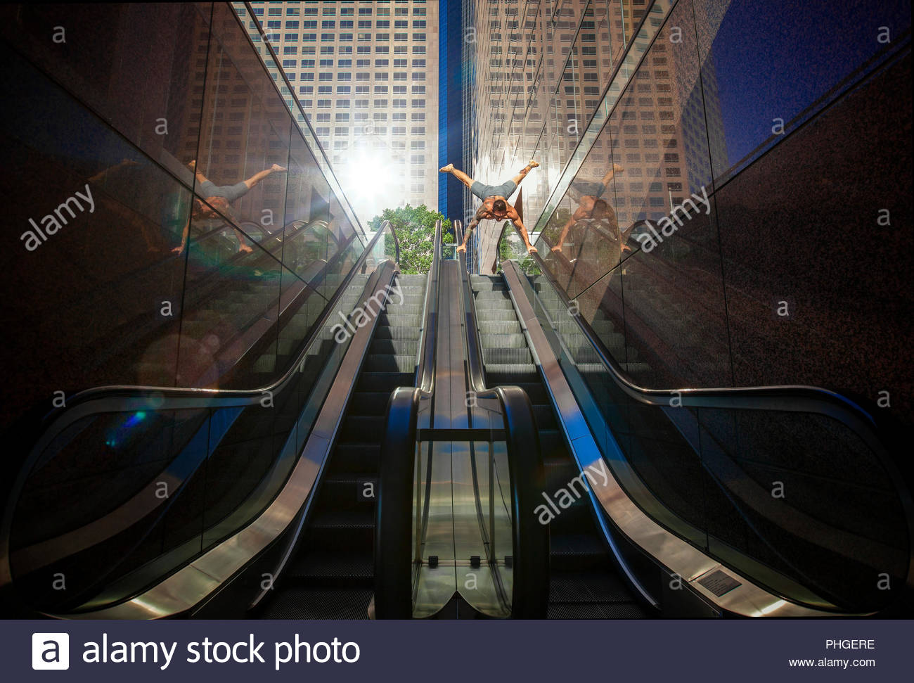 Shirtless man doing handstand on escalator - Stock Image