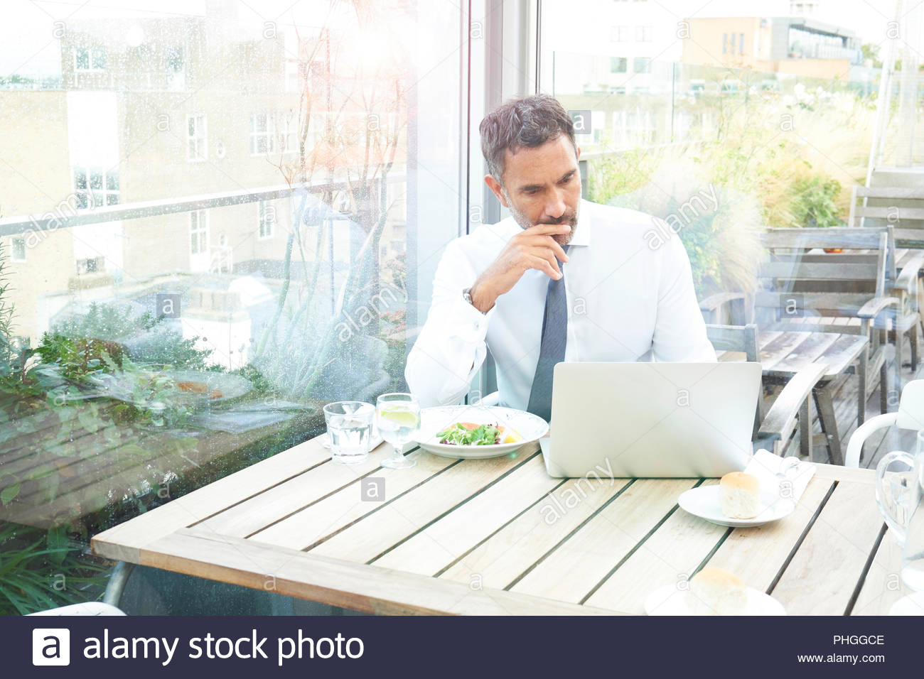 Businessman with laptop by window in restaurant - Stock Image