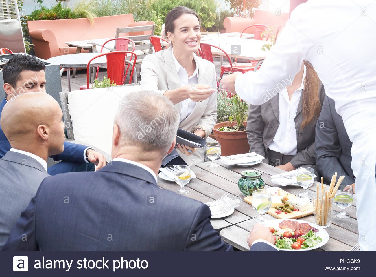 Businesspeople around a table at a restaurant meeting - Stock Image