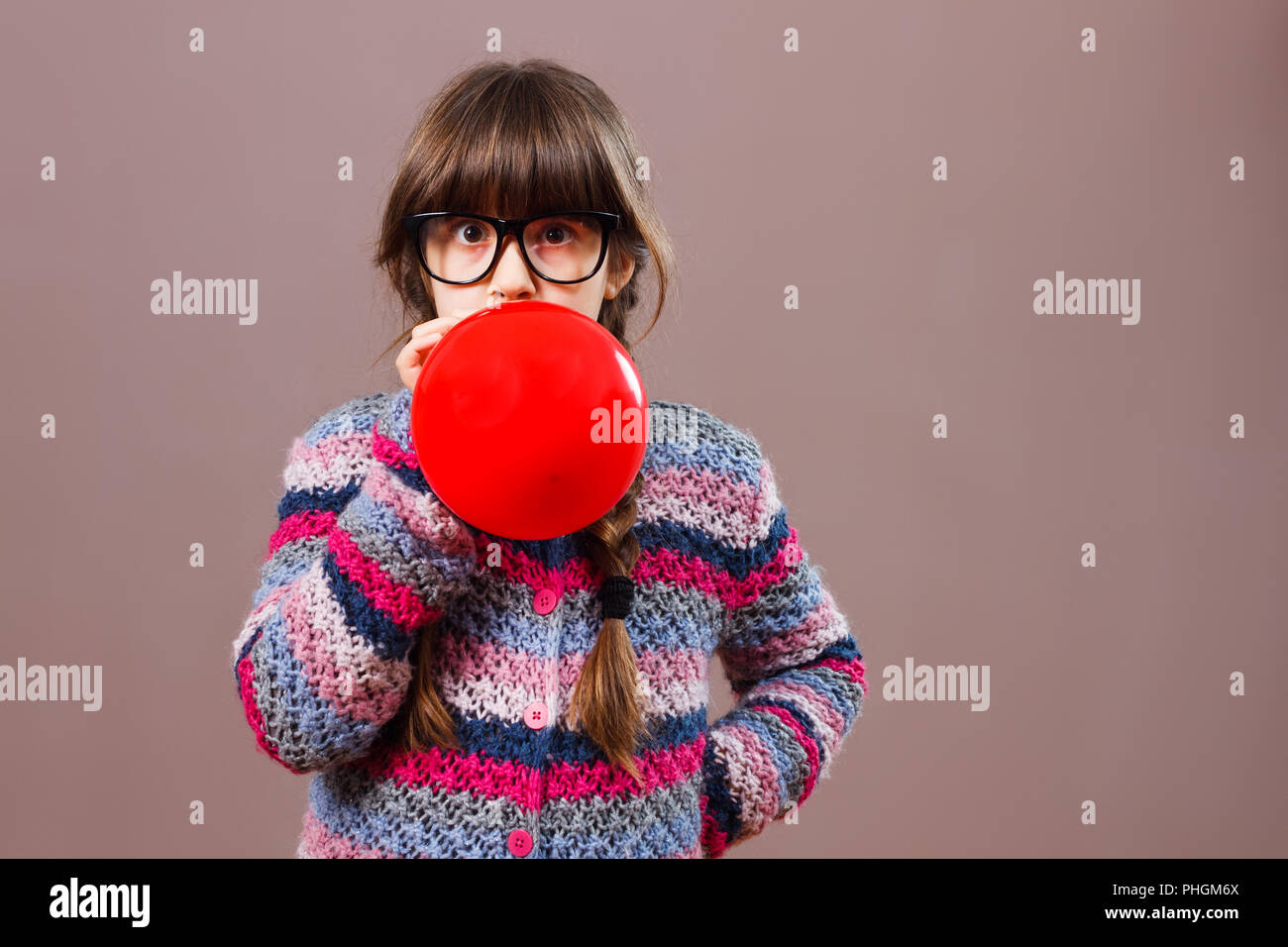 Little nerdy girl blowing balloon - Stock Image
