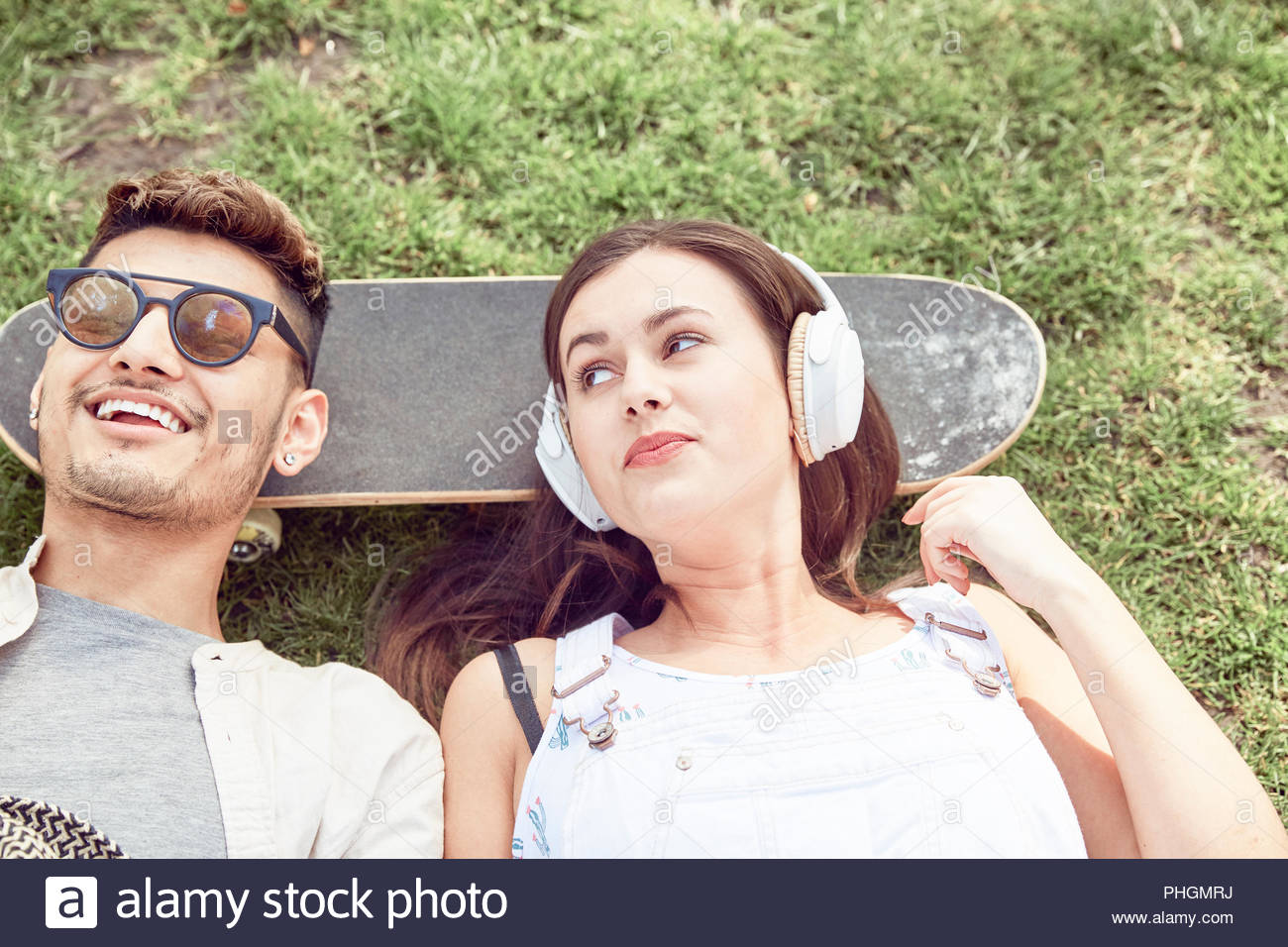 Teenage couple lying on skateboard at park - Stock Image
