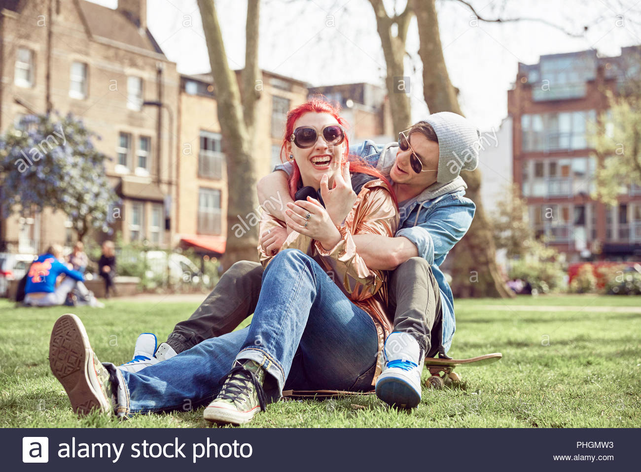 Teenage couple sitting together at park - Stock Image
