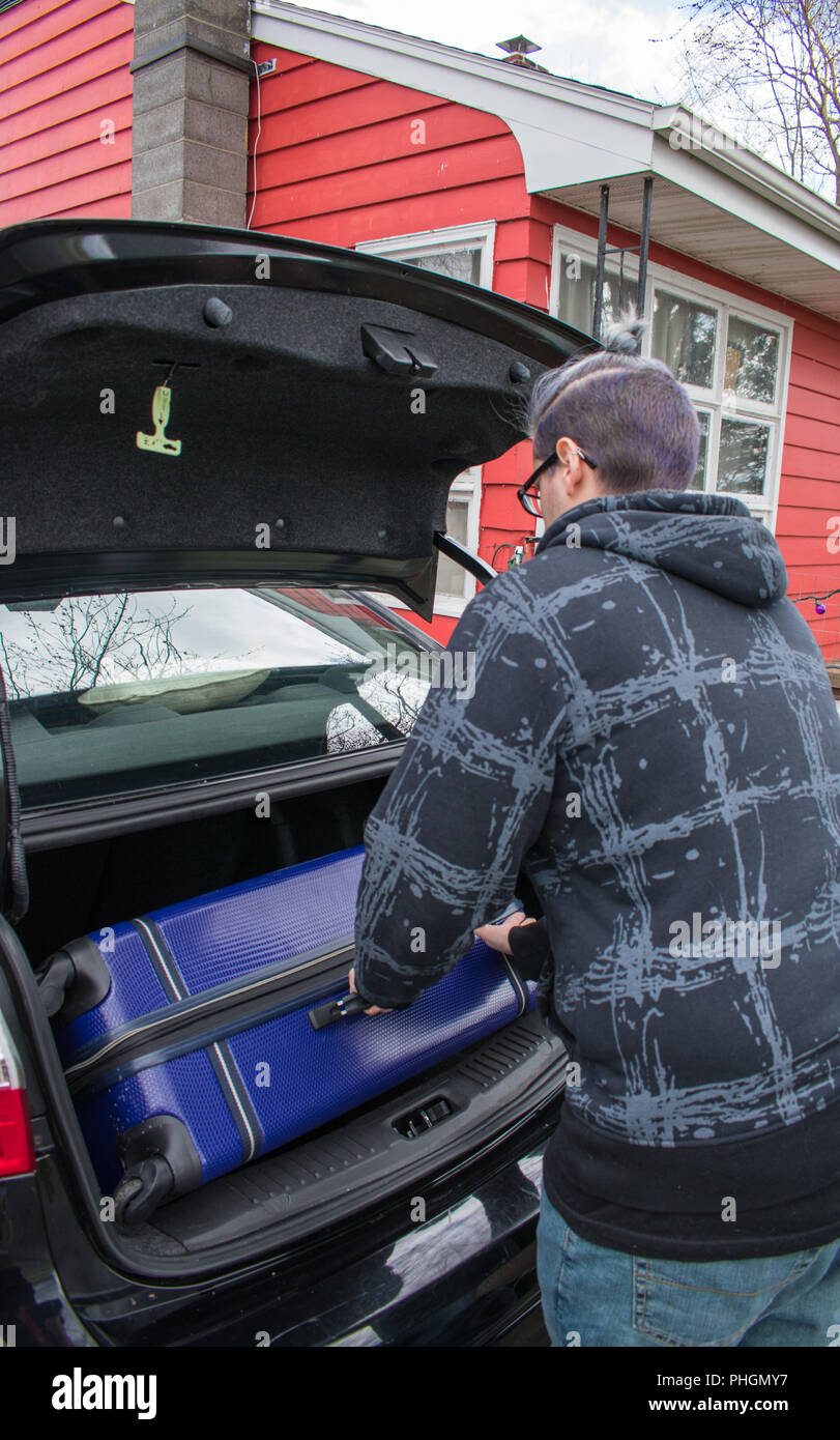 A young man loading luggage into the trunk of a car in preparation for a trip - Stock Image