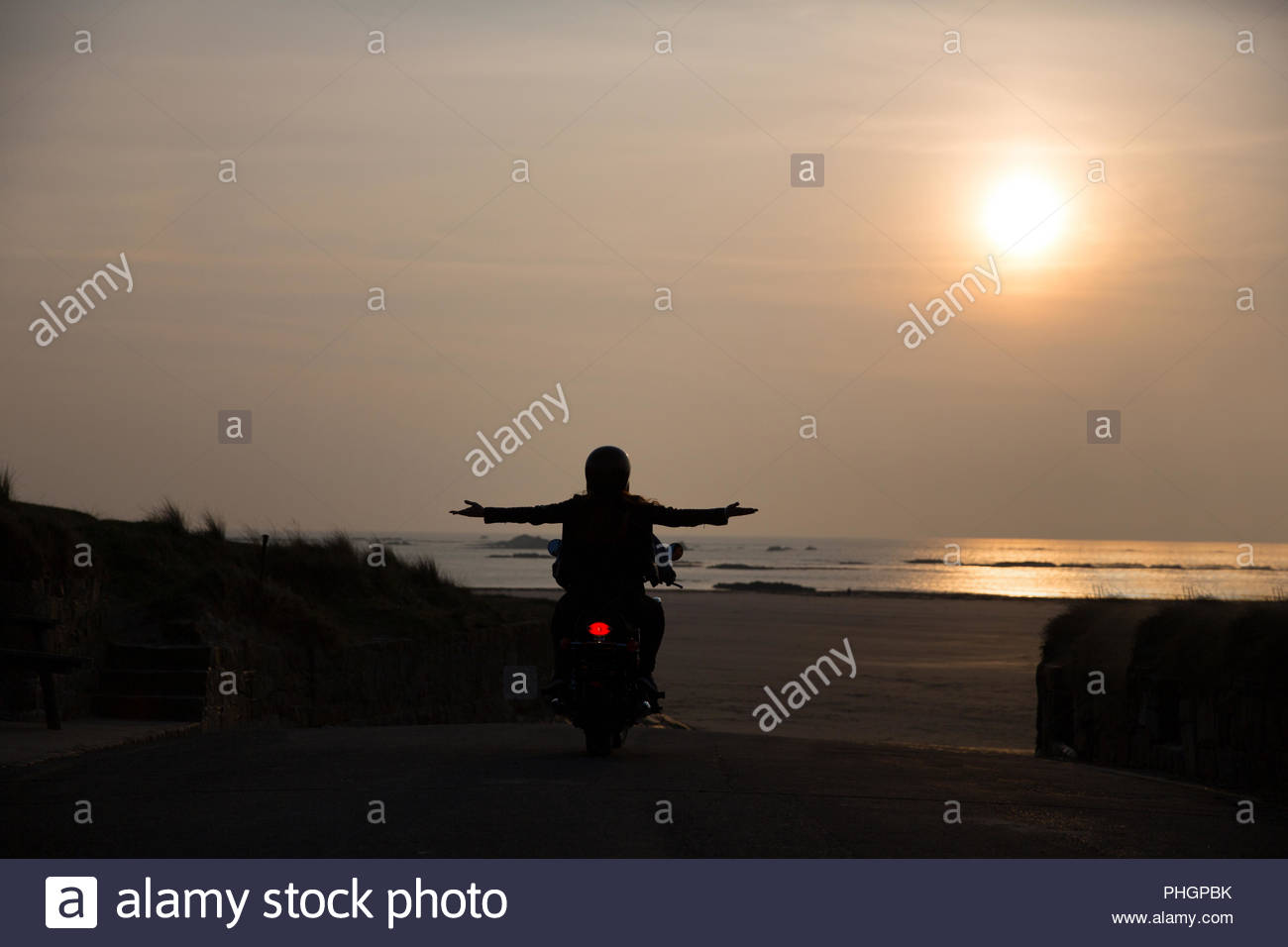 Silhouette of young couple on motorcycle at sunset - Stock Image