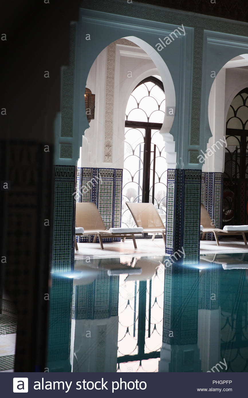Middle Eastern arches and sun loungers by swimming pool - Stock Image