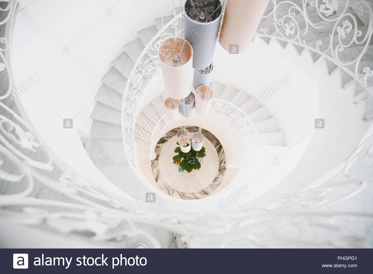 High angle view of pendant lights above a spiral staircase - Stock Image