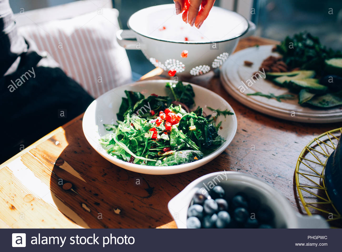 Hand of woman sprinkling pomegranate seeds on salad - Stock Image