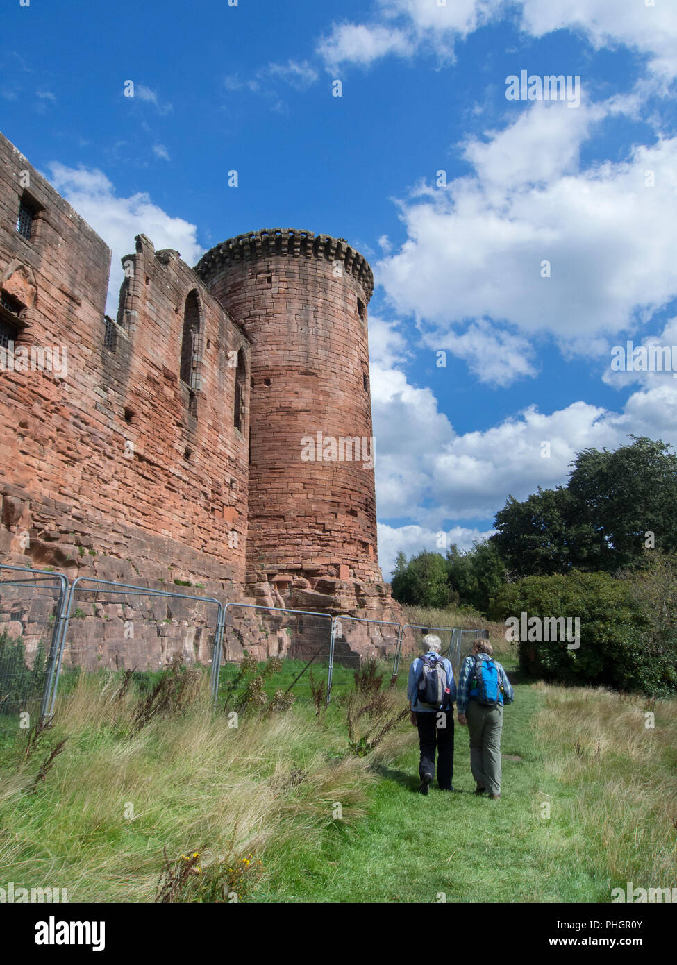 SOUTH LANARKSHIRE, SCOTLAND- AUGUST 31st 2018: Two walkers walking pass Bothwell Castle. - Stock Image