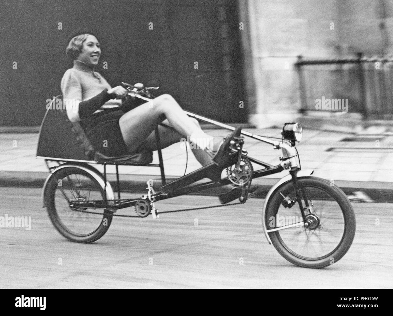 The Velocar 1933. The new horizontal bicycle is launched ath the Light Cycle Exhibition held at the Horticultural Hall at Westminster. Instead of sitting upright, the rides sits in an armchair position and pushes forwards with the legs. Pictures here Mrs. Evelyn Hamilton, champion cyclist,trying out the new Velocar bicycle. November 15 1933 More info on Evelyn Hamilton: http://classicpicturelibrary.blogspot.com/2018/08/record-breaking-woman-cyclist.html - Stock Image