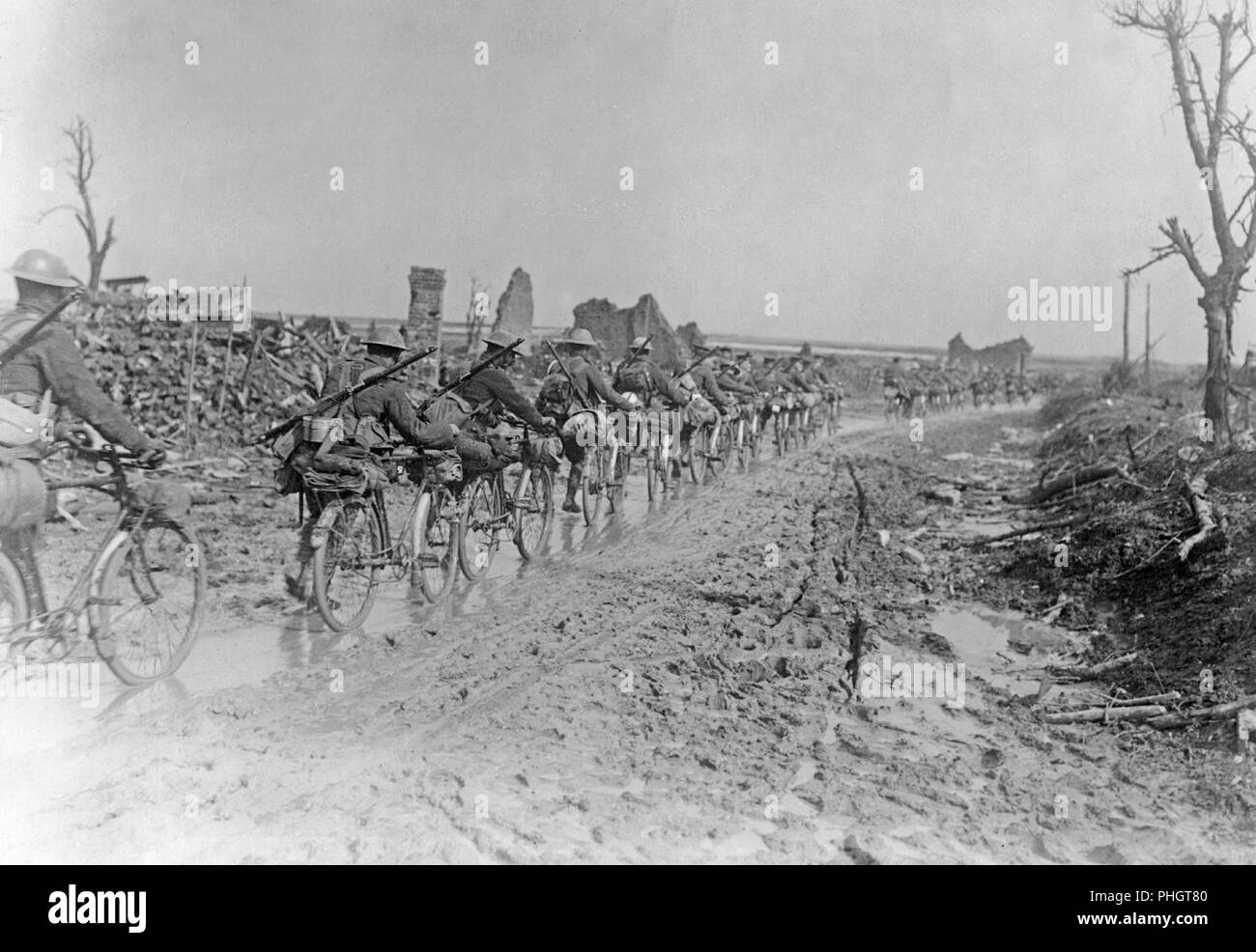 First World War 1914-1918. British soldiers with their bicycles are walking on a muddy road somewhere in France. They are passing demolished buildings and ruins. - Stock Image