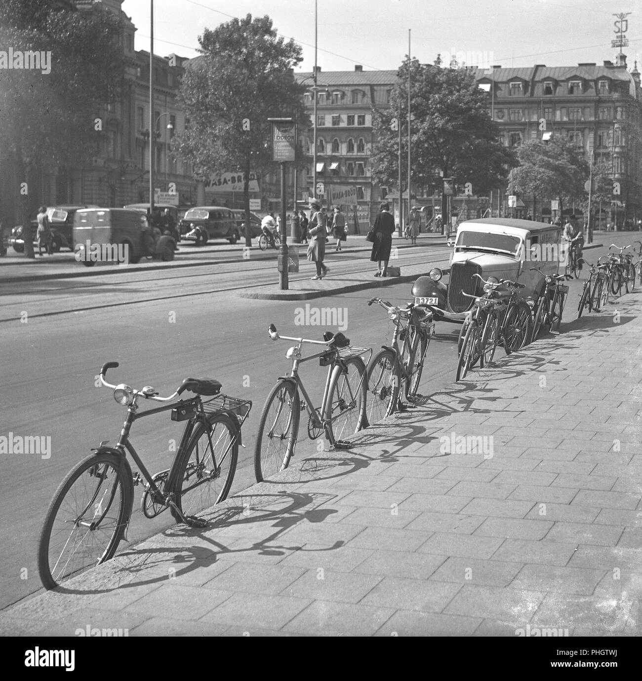 1940s cyclists. Bicycles are parked against the sidewalk in a busy street in Stockholm city. The stand for parking the bicycle without leaning it to something, looks as if it is not yet an item mounted on the bicycles. The bicycles are all leaning agains the kerb of the sidewalk.  May 1940.  Photo Kristoffersson 129-9 - Stock Image