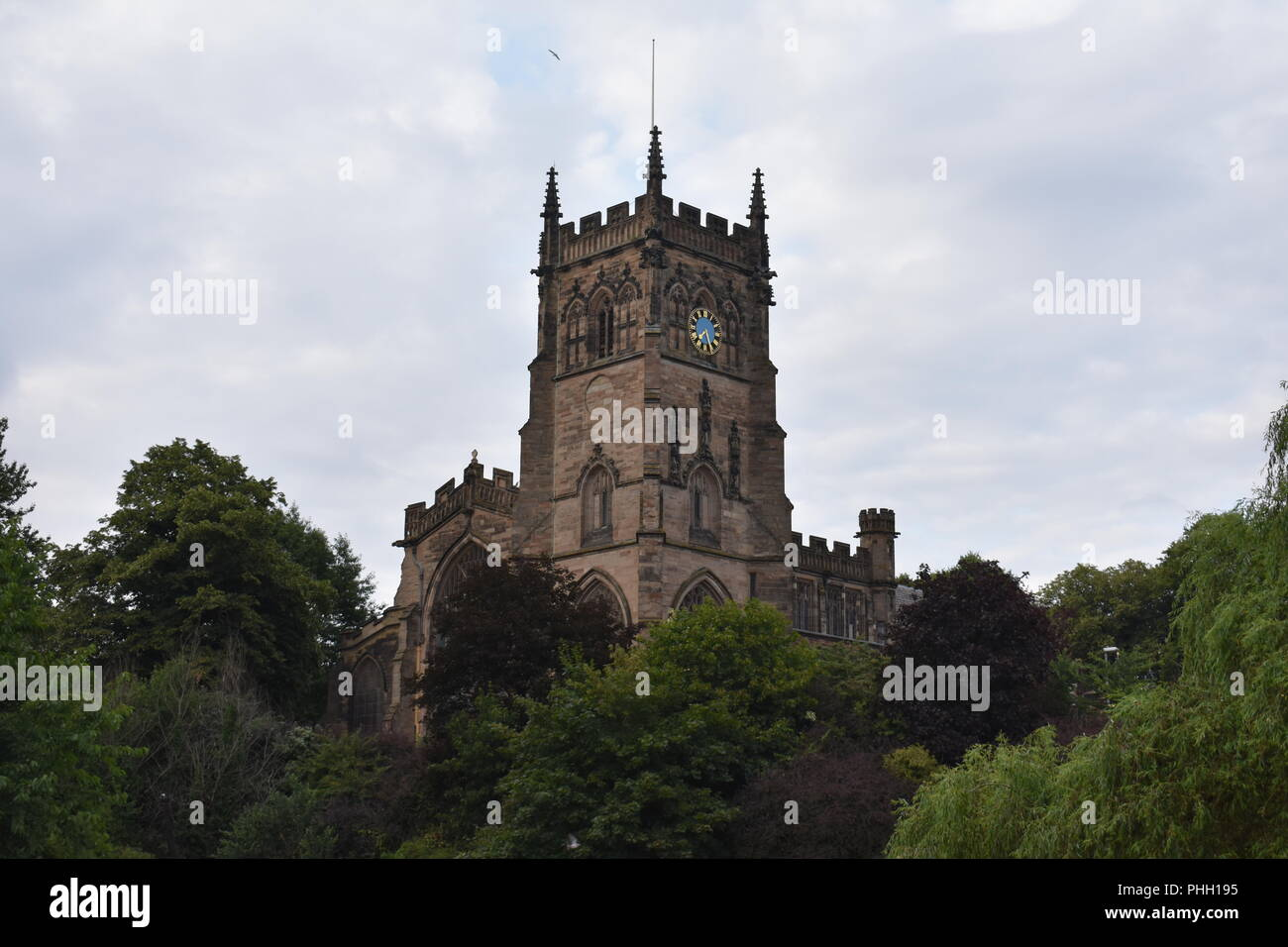 St Mary and All Saints' Church, Kidderminster. Against a cloudy sky, with trees in the foreground. - Stock Image