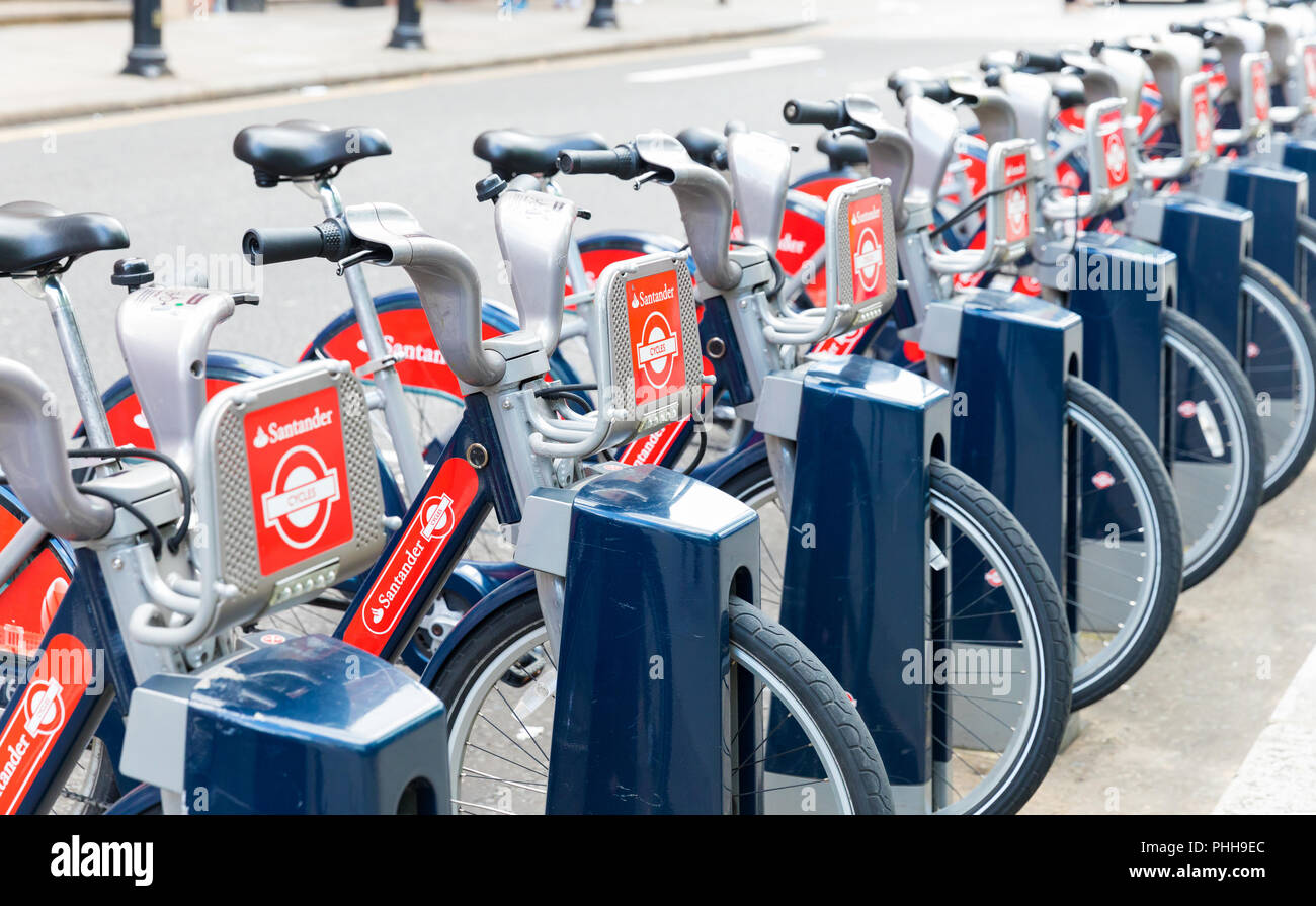 LONDON, ENGLAND, UK - 31 JULY, 2017: Row of Santander red public rental hire bicycles at docking station, known as Boris Bikes - Stock Image