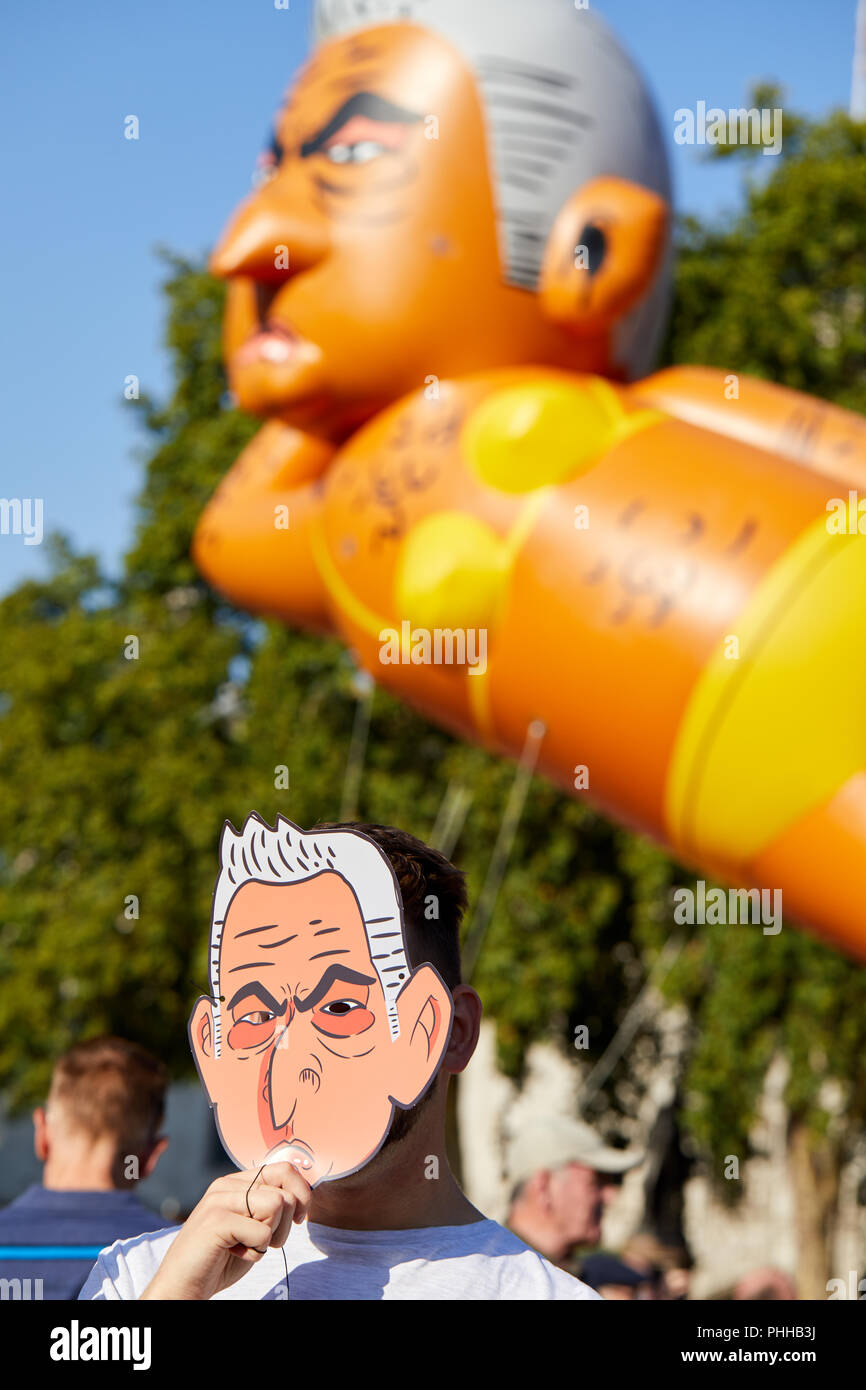 London, U.K. - 1 September 2018: A protestor displaying a Sadiq Khan mask watches a balloon mocking the London mayor as it is flown in Parliament Square. Credit: Kevin Frost/Alamy Live News - Stock Image