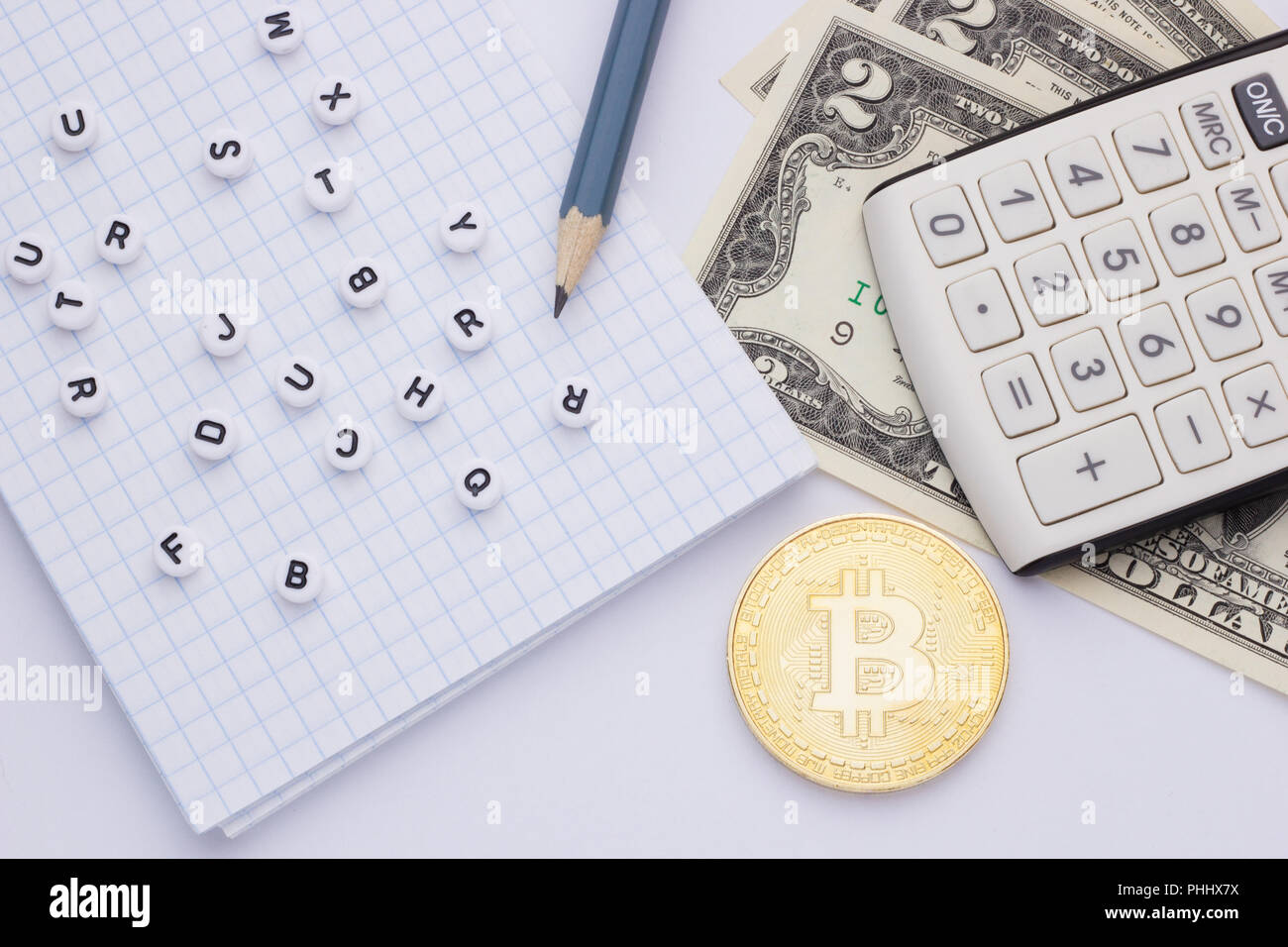 close-up, on a white background calculator, money (bitcoin) and