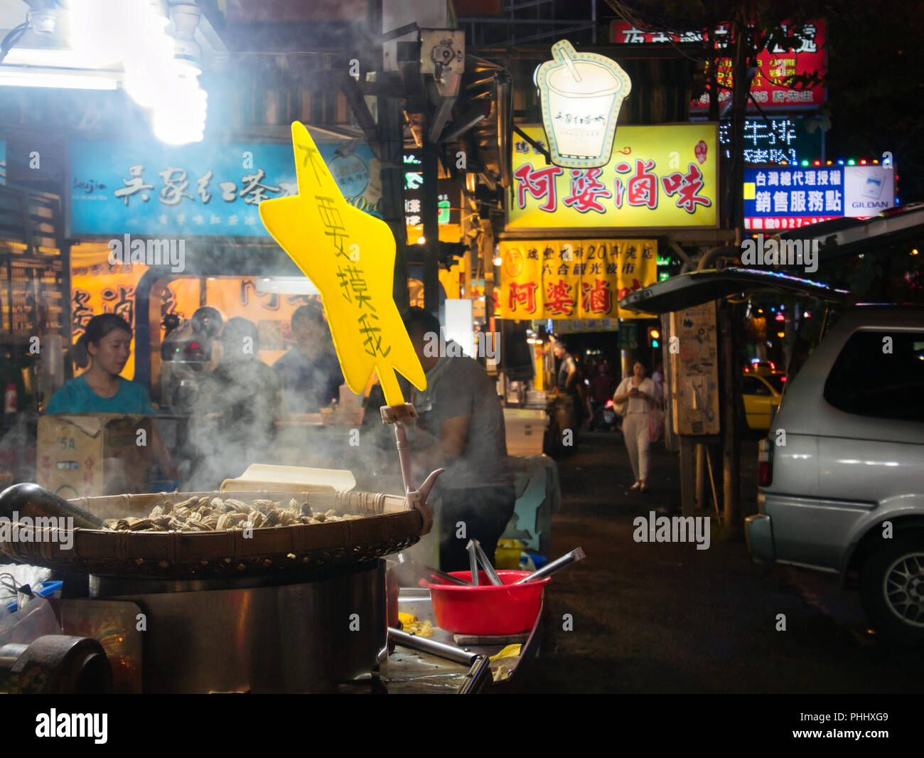 Peanuts being roasted in steaming big pan at taiwanese night market RuiFeng in Kaohsiung, Taiwan - Stock Image