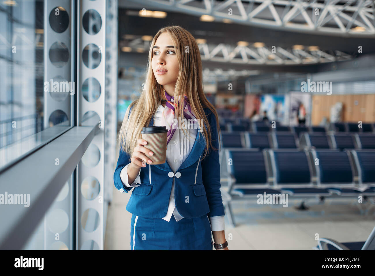 Stewardess with suitcase and coffee against window in airport. Air hostess with baggage in waiting room, flight attendant with hand luggage, aviatrans - Stock Image
