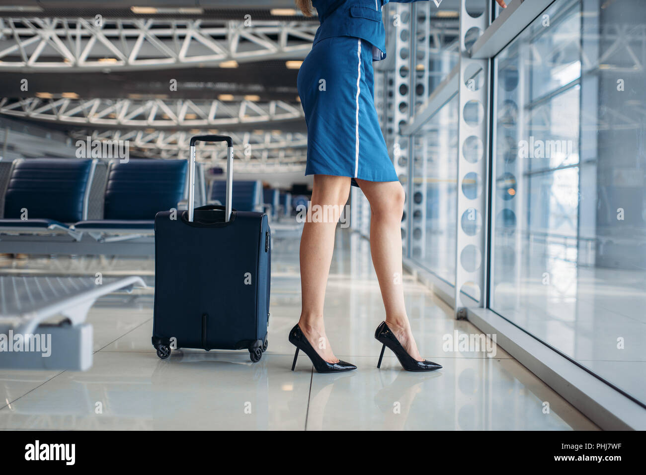 Slender stewardess and suitcase against window in airport hall. Air hostess with baggage in departure area, flight attendant with hand luggage, aviatr - Stock Image