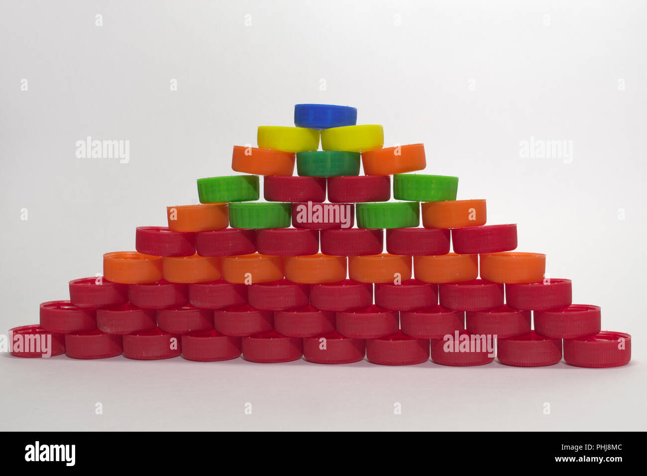 pyramid with blue top element. made out of multicolored bottle caps - Stock Image