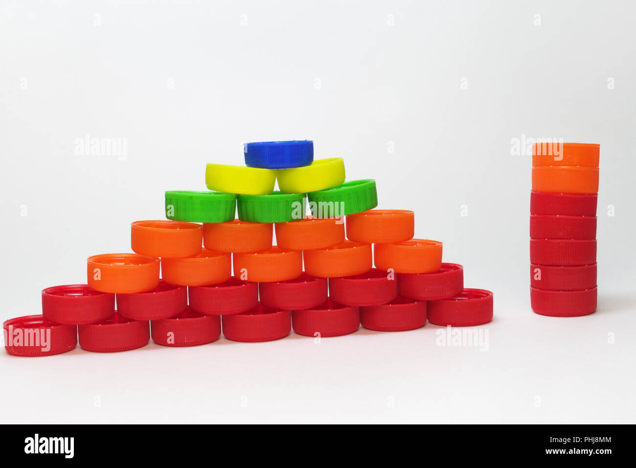 pyramid made out of plastic ribbed bottle caps and column of the same caps, stowed in the same height. reuse and recycle - Stock Image