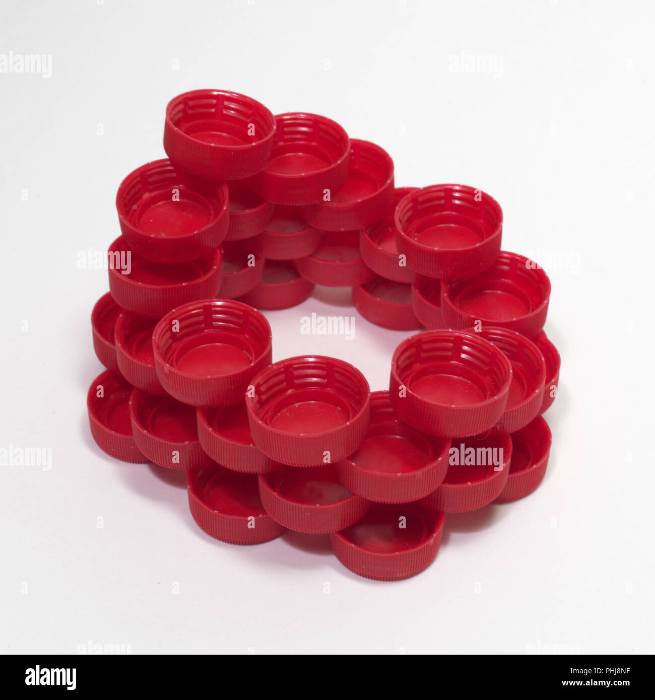 funny shape of plastic bottle caps, folded into round unfinished wall. square frame - Stock Image