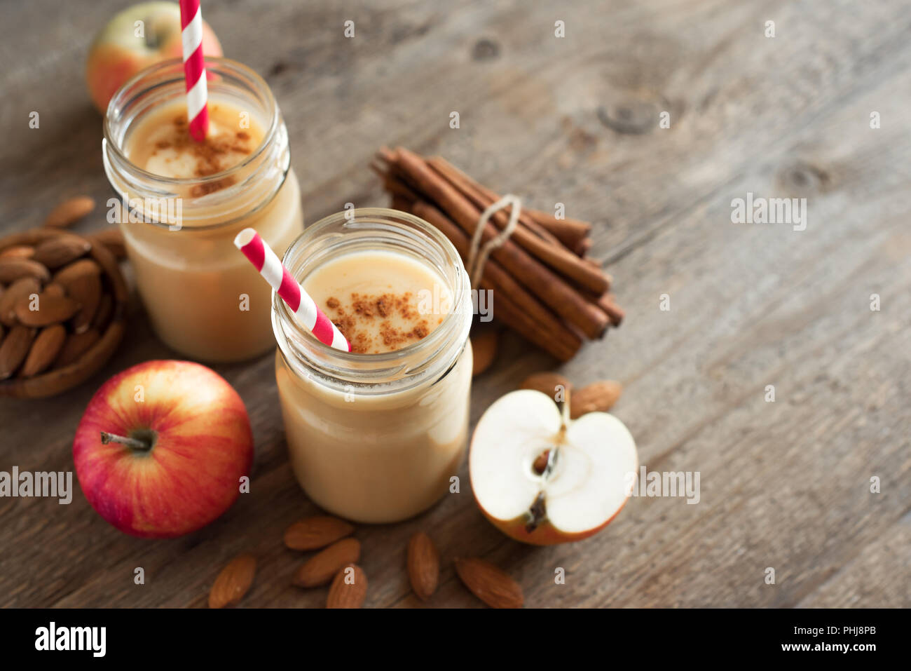 Apple pie protein smoothie drink with almond milk. Homemade apple smoothie with apple pie spices (cinnamon) on wooden background, copy space. Stock Photo