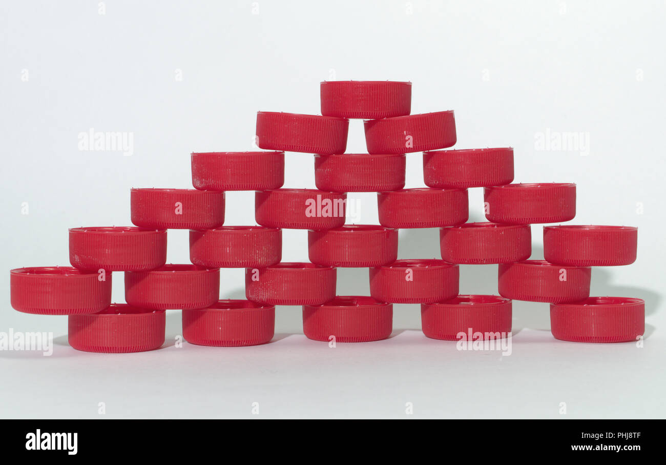 holey wall pattern of red ribbed plastic bottle caps, relying on each other by the tips of narrow edges. folded by layers in rows - Stock Image