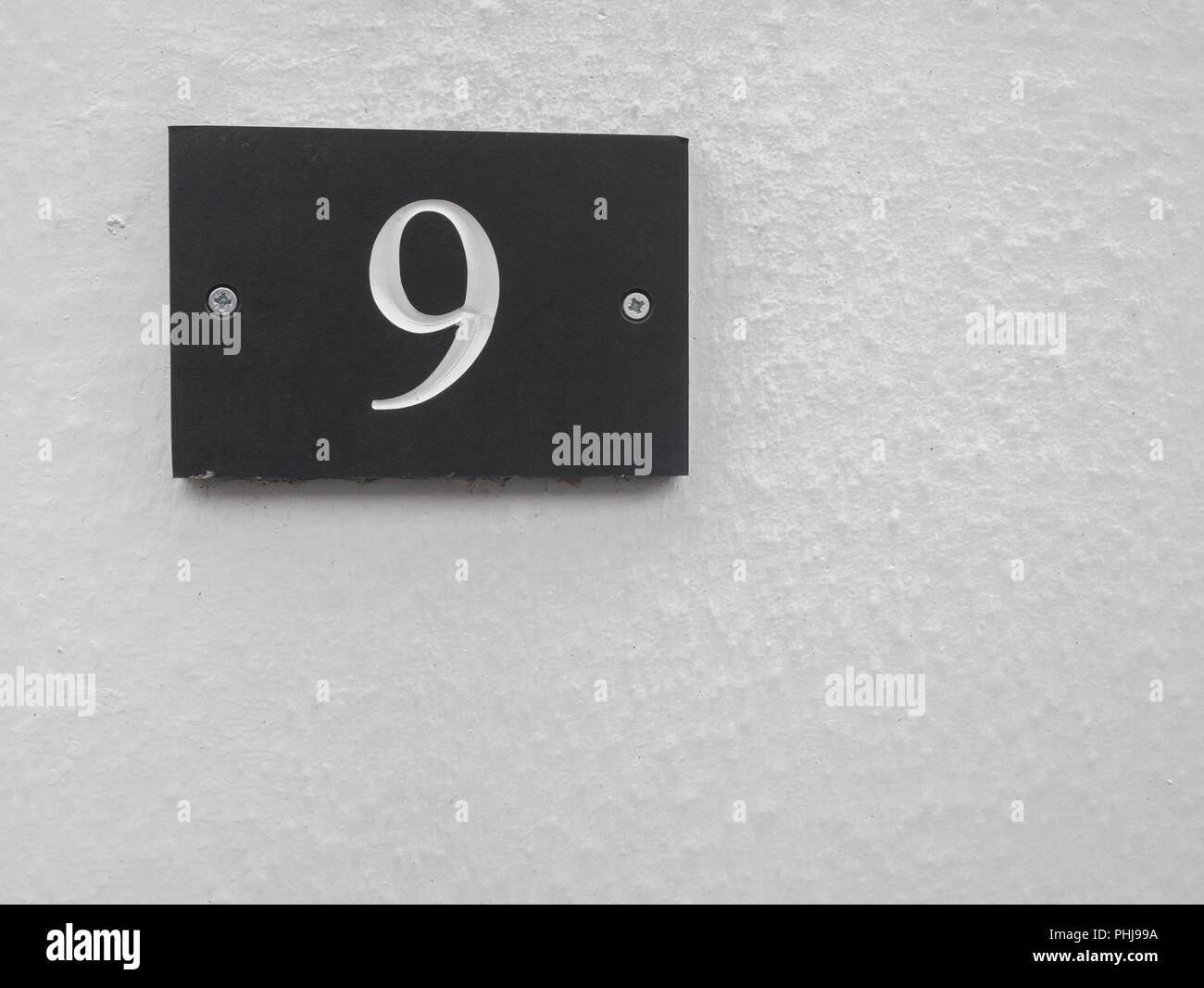 House wall with a Number 9 plaque. Odd number. - Stock Image