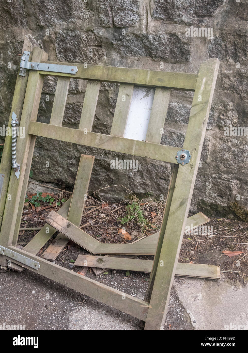 Broken / smashed garden gate propped against stone wall. - Stock Image