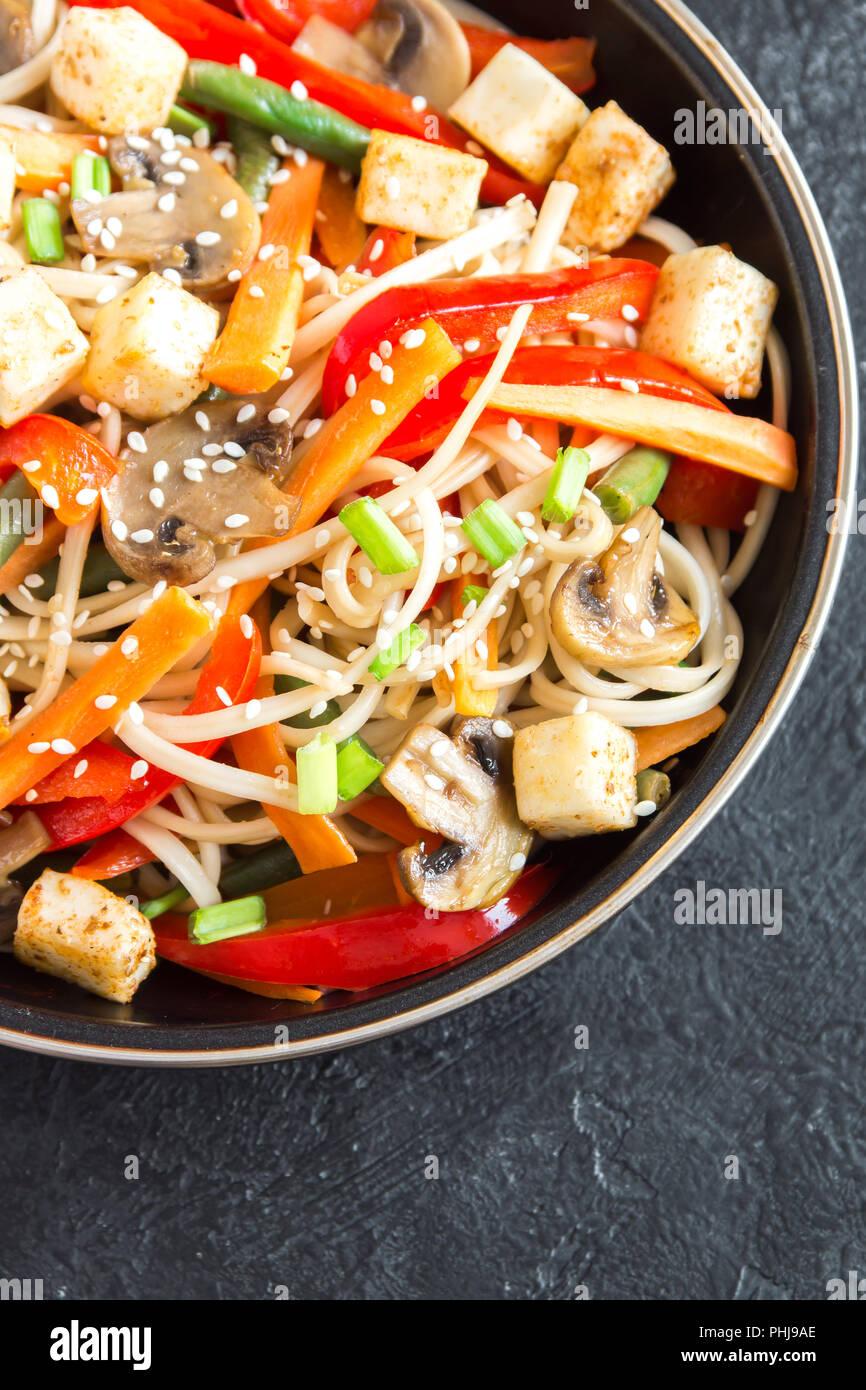 Stir fry with udon noodles, tofu, mushrooms and vegetables. Asian vegan vegetarian food, meal, stir fry in wok over black background, copy space. - Stock Image