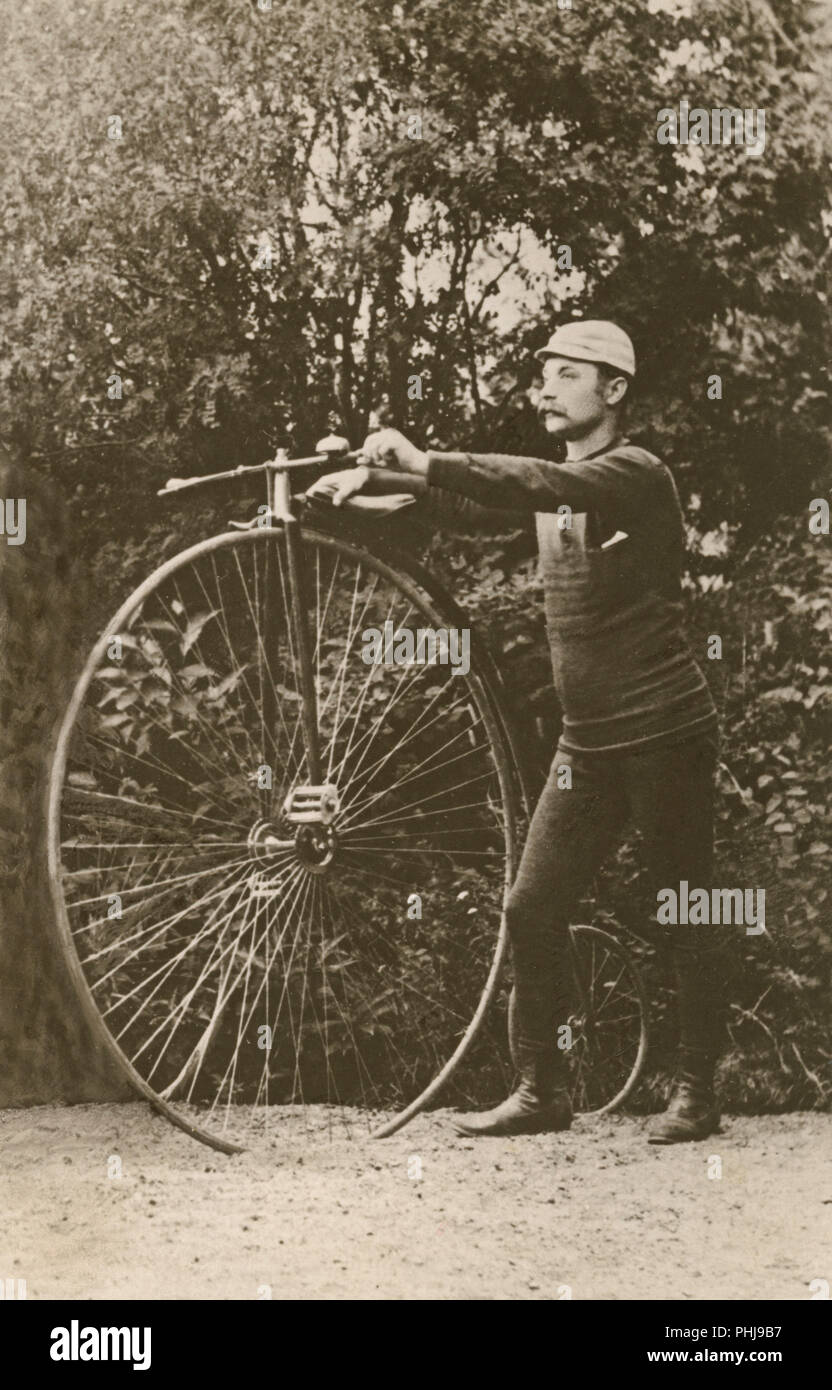 Penny farthing bicycle. A man is standing beside a penny-farthing bicycle. A bicycycle model with a large front wheel and a small back wheel. Sweden 1880s - Stock Image