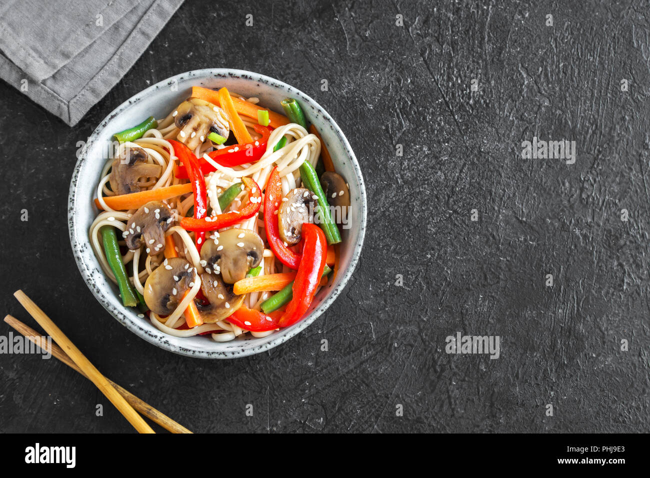 Stir fry with udon noodles, mushrooms and vegetables in bowl. Asian vegan vegetarian food, meal, stir fry over black background, copy space. Stock Photo