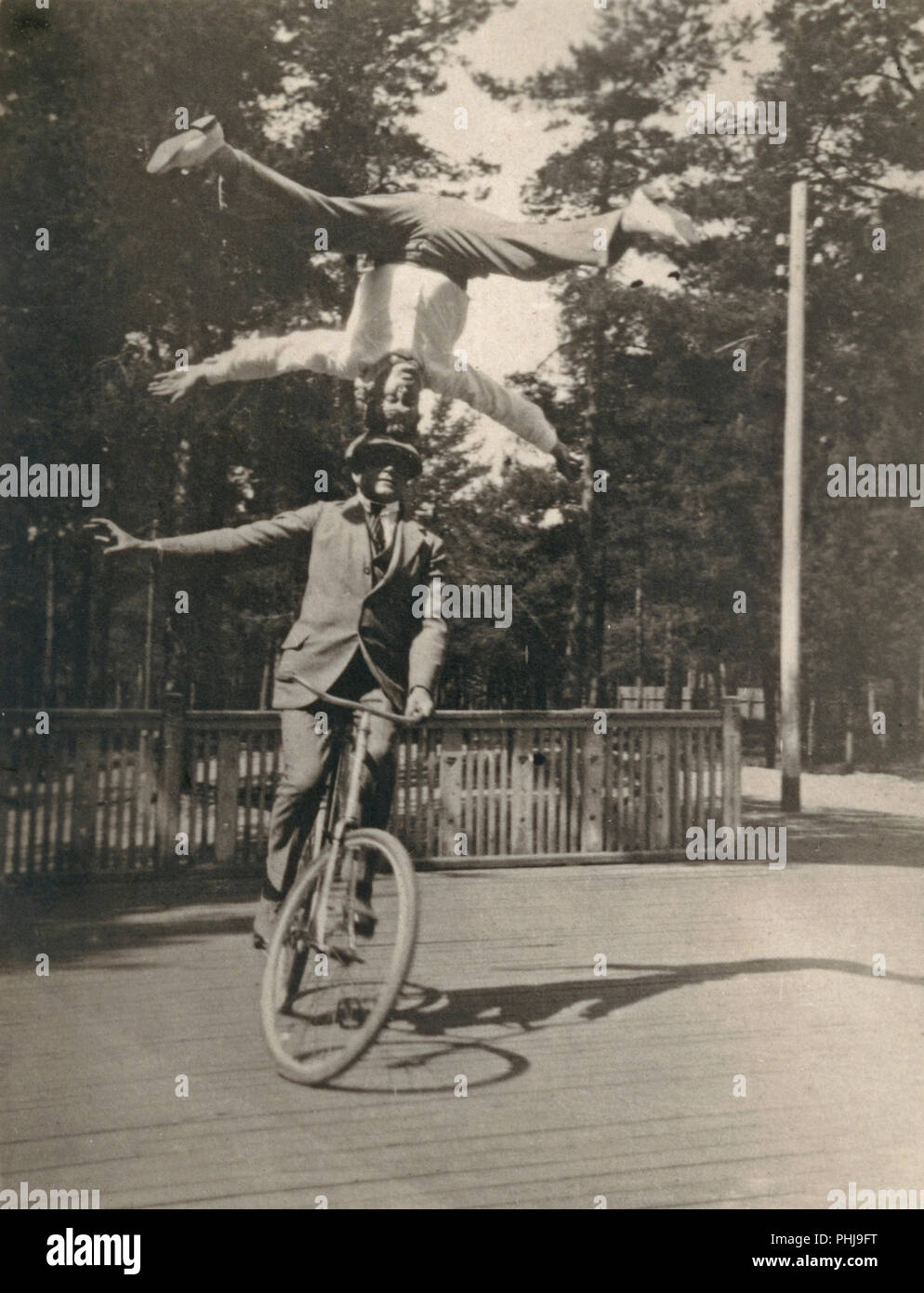 1920s men on a bicycle. The Swedish bicycle acrobat Fritiof Malmsten is performing his balance act with his young brother Helge. An impressive performance where he is standing on his head and not using his hands to hold his balance. Fritiof Malmsten became a internationally known bicycle acrobat. - Stock Image