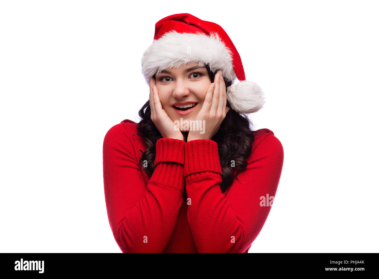 Portrait of joyful woman wearing santa hat in red sweater, smiling broadly and holding palms near cheeks, isolated over white background - Stock Image