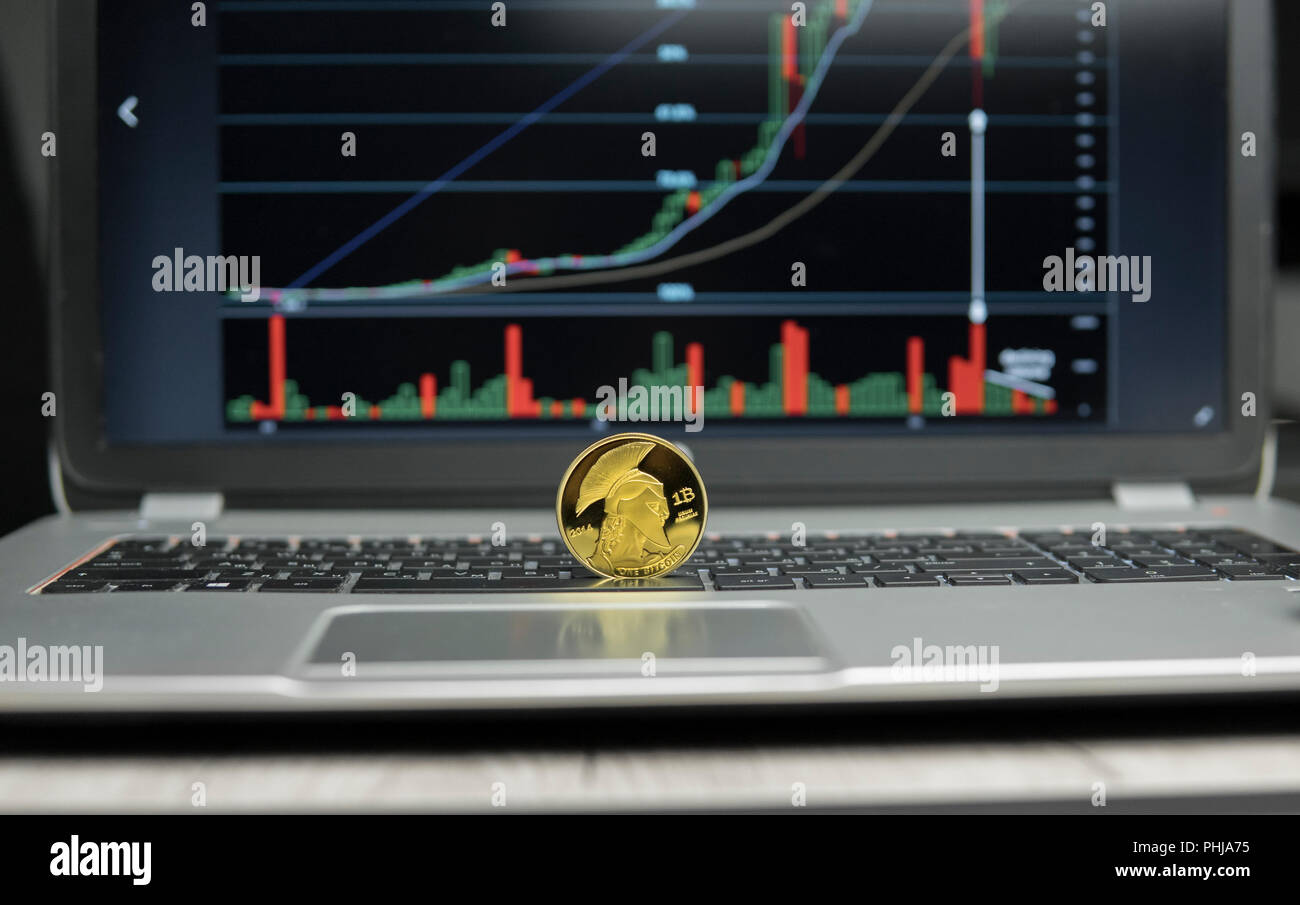 golden titan bitcoin coin on a silver keyboard of laptop and diagram chart  graph on a screen as a background  virtual cryptocurrency concept