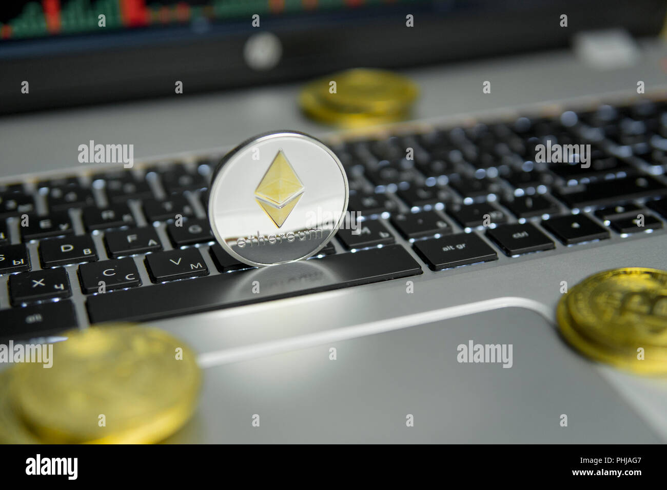 Golden Silver Ethereum Coin With Gold Coins Lying Around On A Black