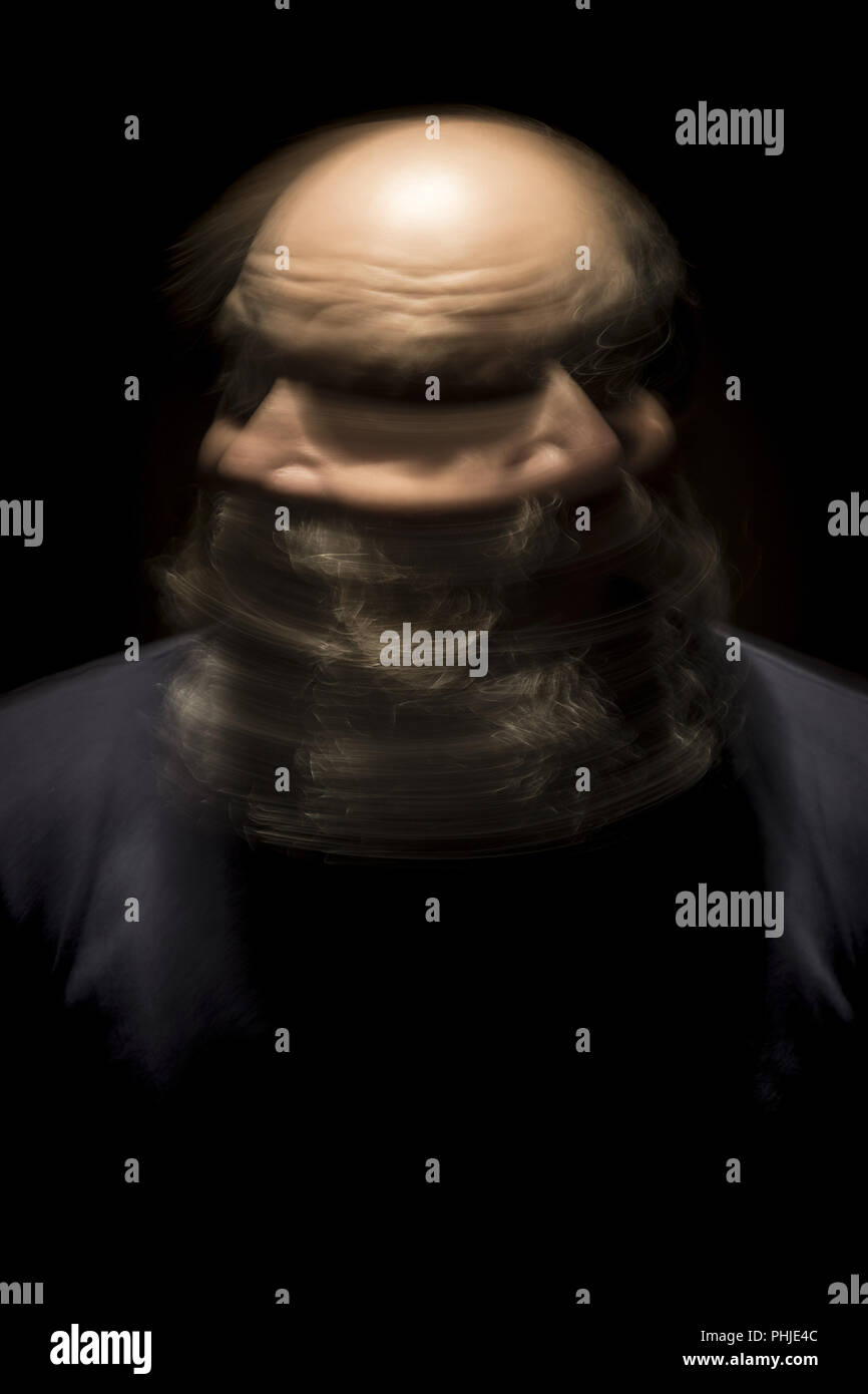 motion blur portrait of a bearded bald head man - Stock Image