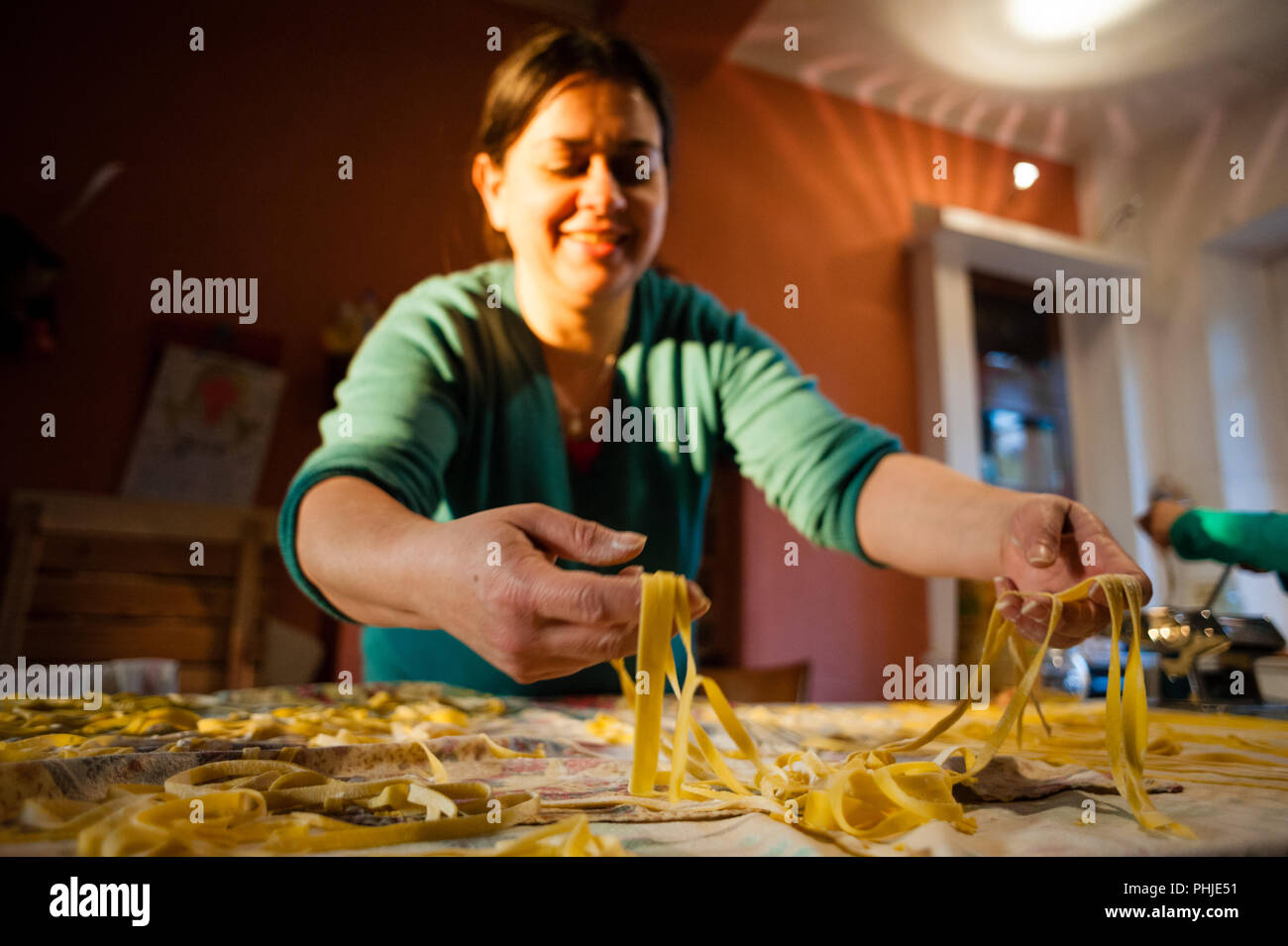 40 year old woman prepares fresh egg pasta homemade noodles - Stock Image