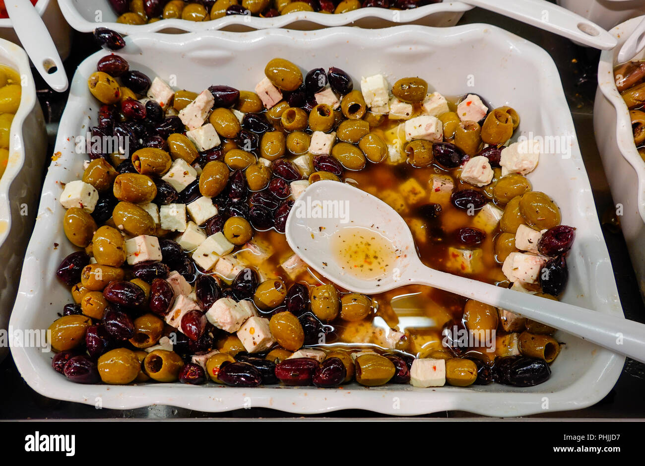 Olives and other savories in a cold ready to eat selection in a supermarket - Stock Image