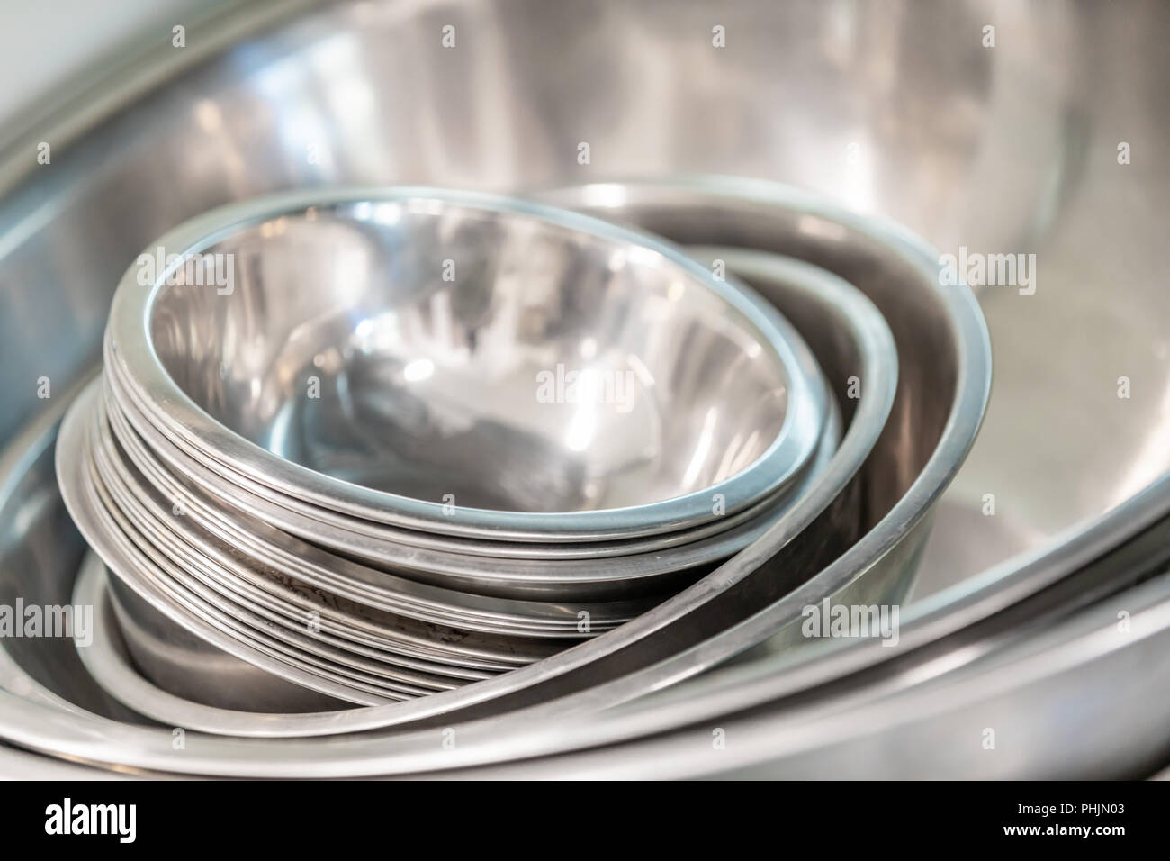 detail image of a set of nesting stainless steel bowls in a commercial kitchen - Stock Image