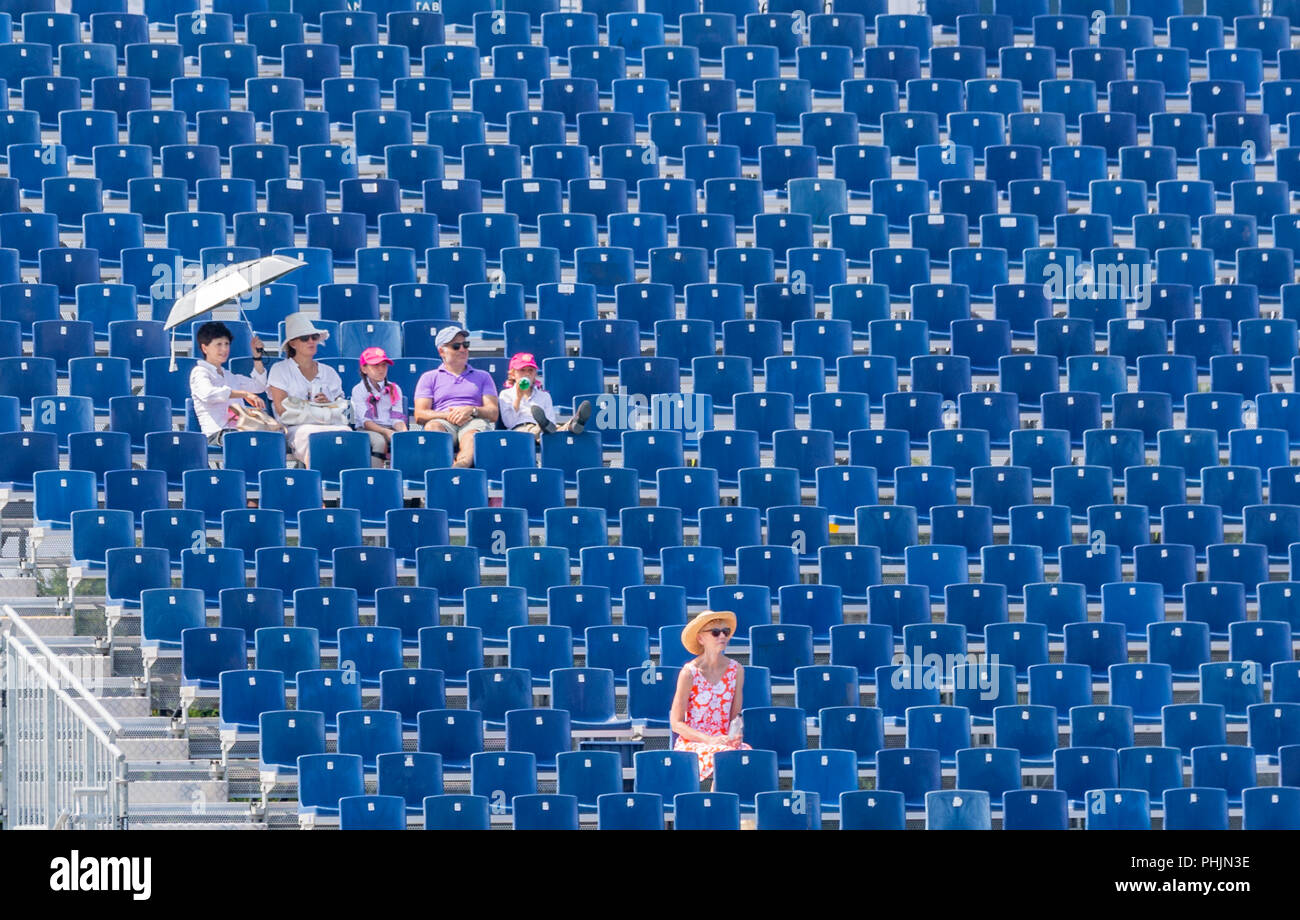 a group of five people sitting in the blue bleachers and one woman sittling alone - Stock Image